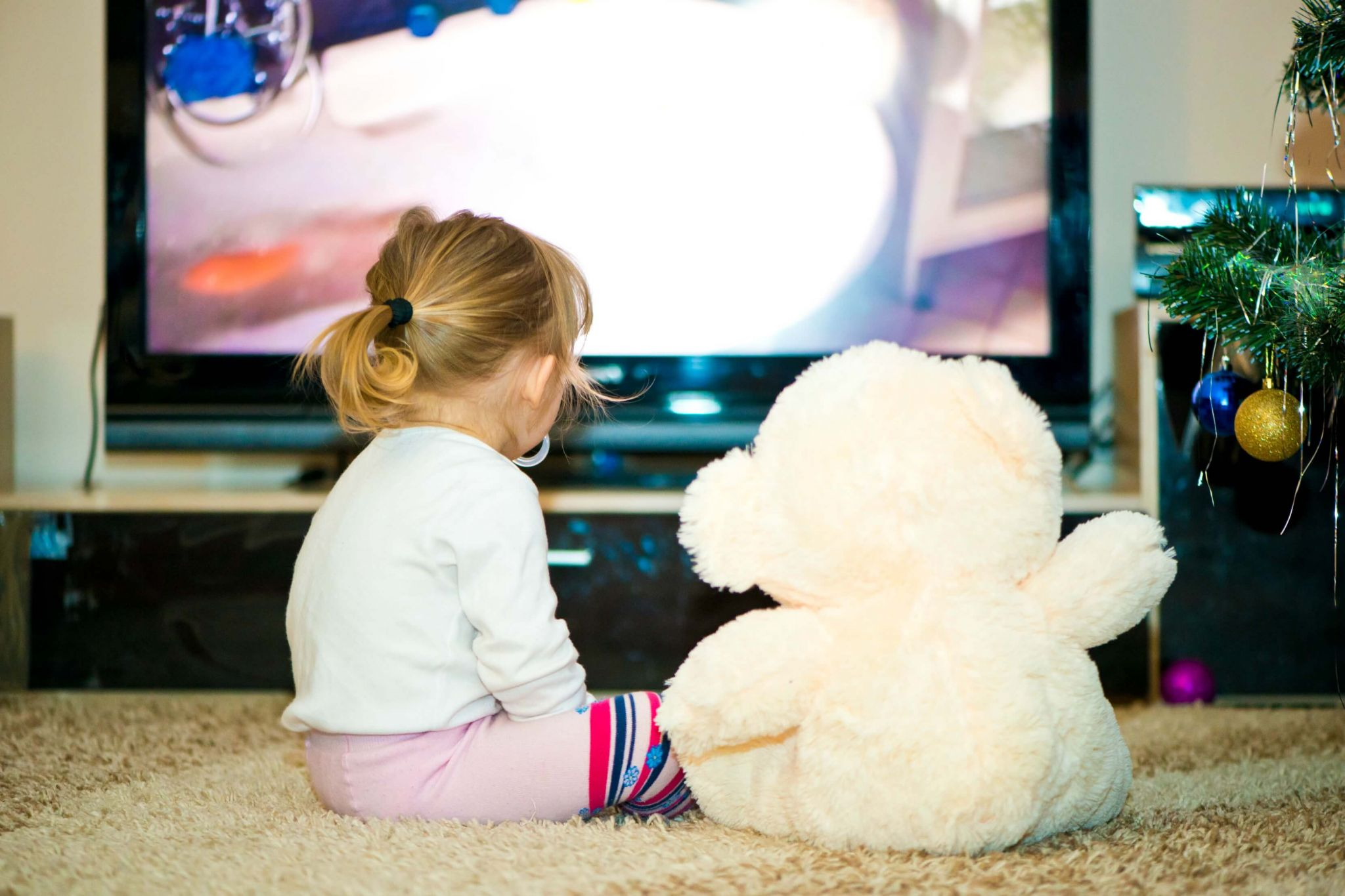 should you let your toddler watch TV - little girl watching TV with her teddy bear