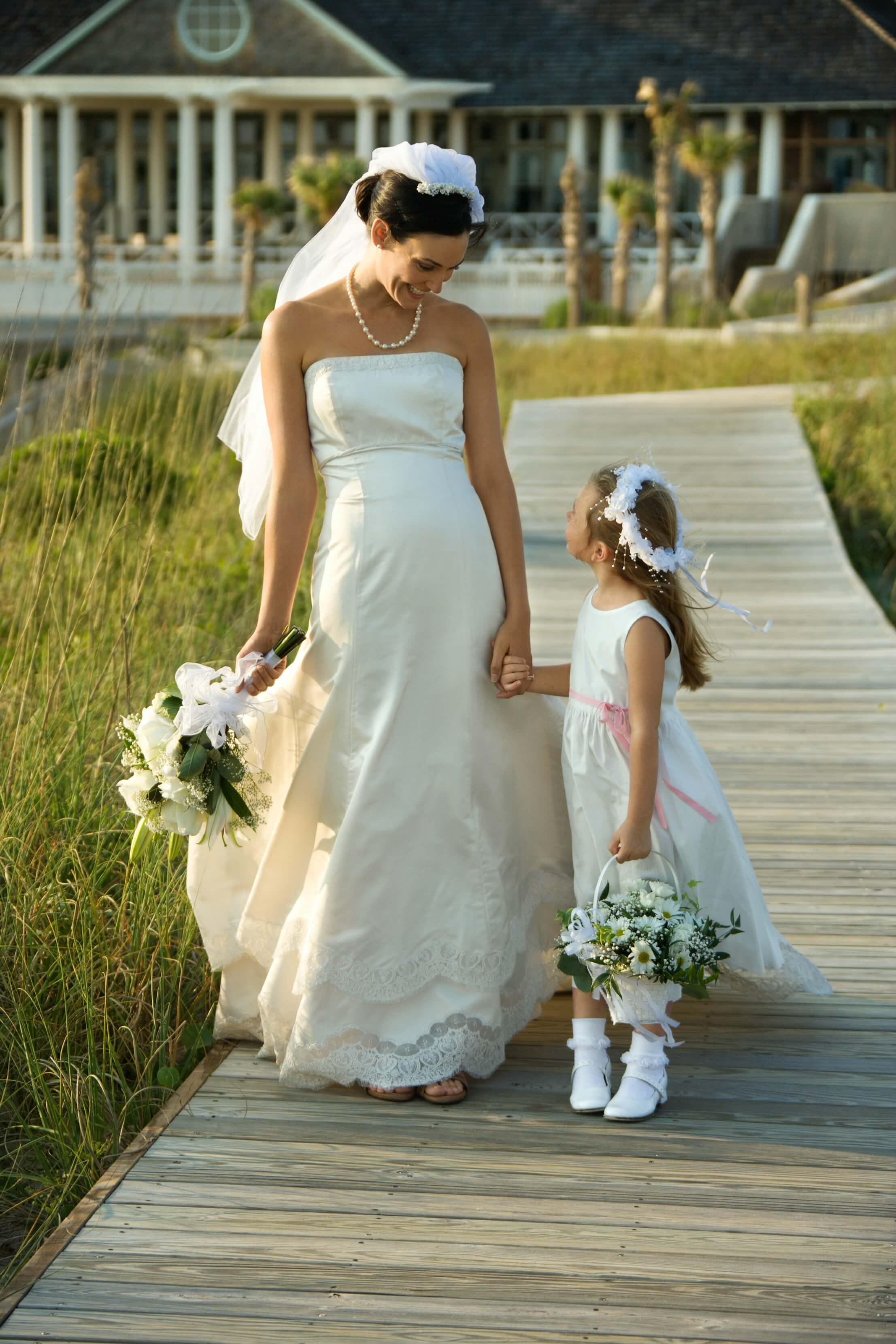 taking your child out of school to attend your wedding - bride and flower girl on boardwalk surrounded by reeds