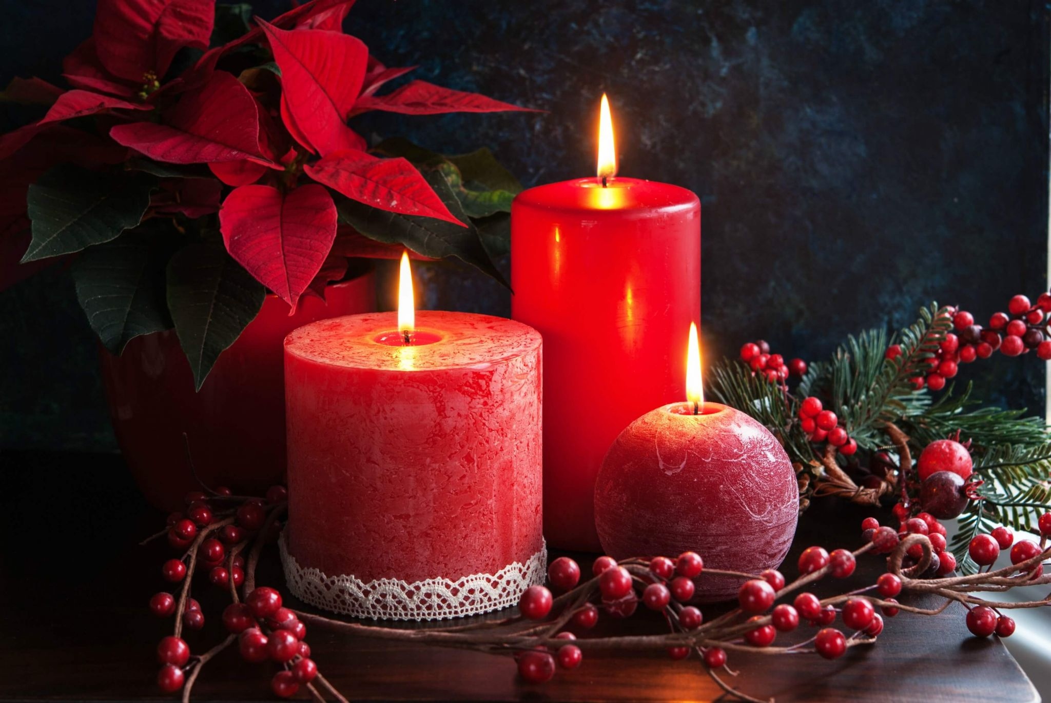 Poinsettia care - Christmas candles, berries and a poinsettia
