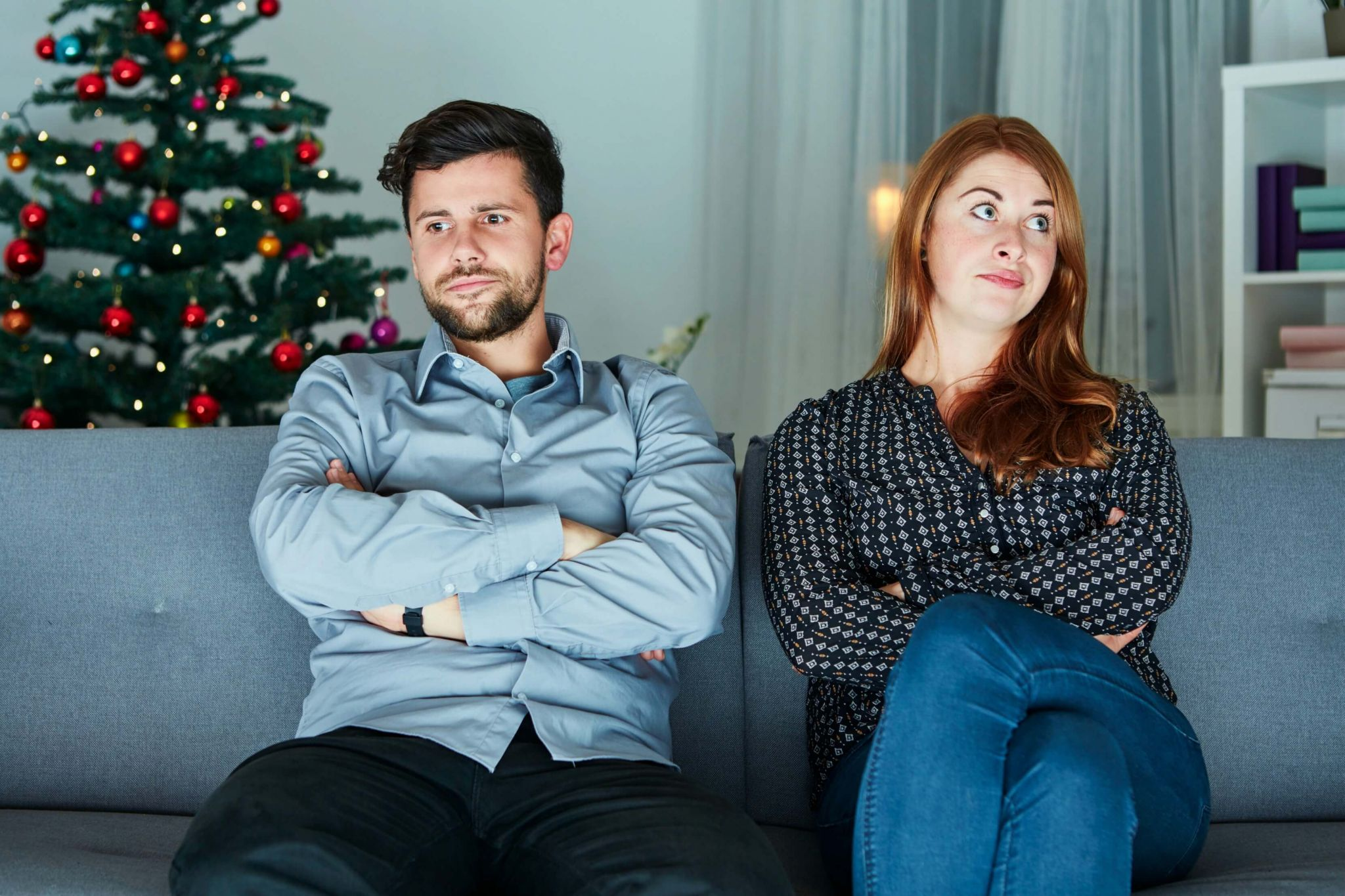Christmas arguments - couple on the sofa not speaking at Christmas