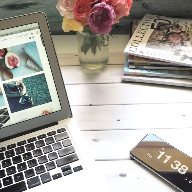 blog about your job - desk with macbook, periodicals and roses in a vase