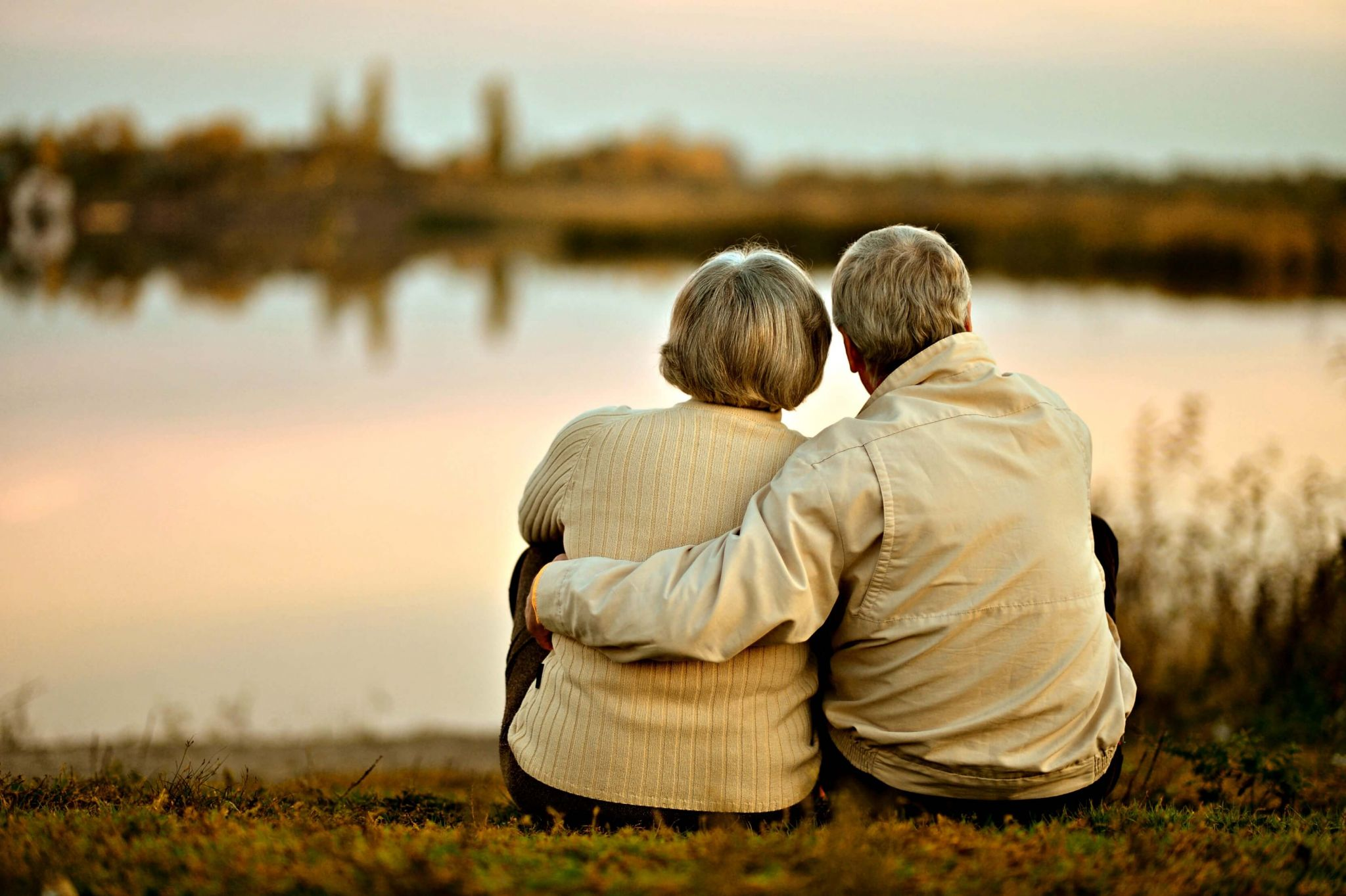 taking care of our parents - elderly couple sat together by a lake at sunset