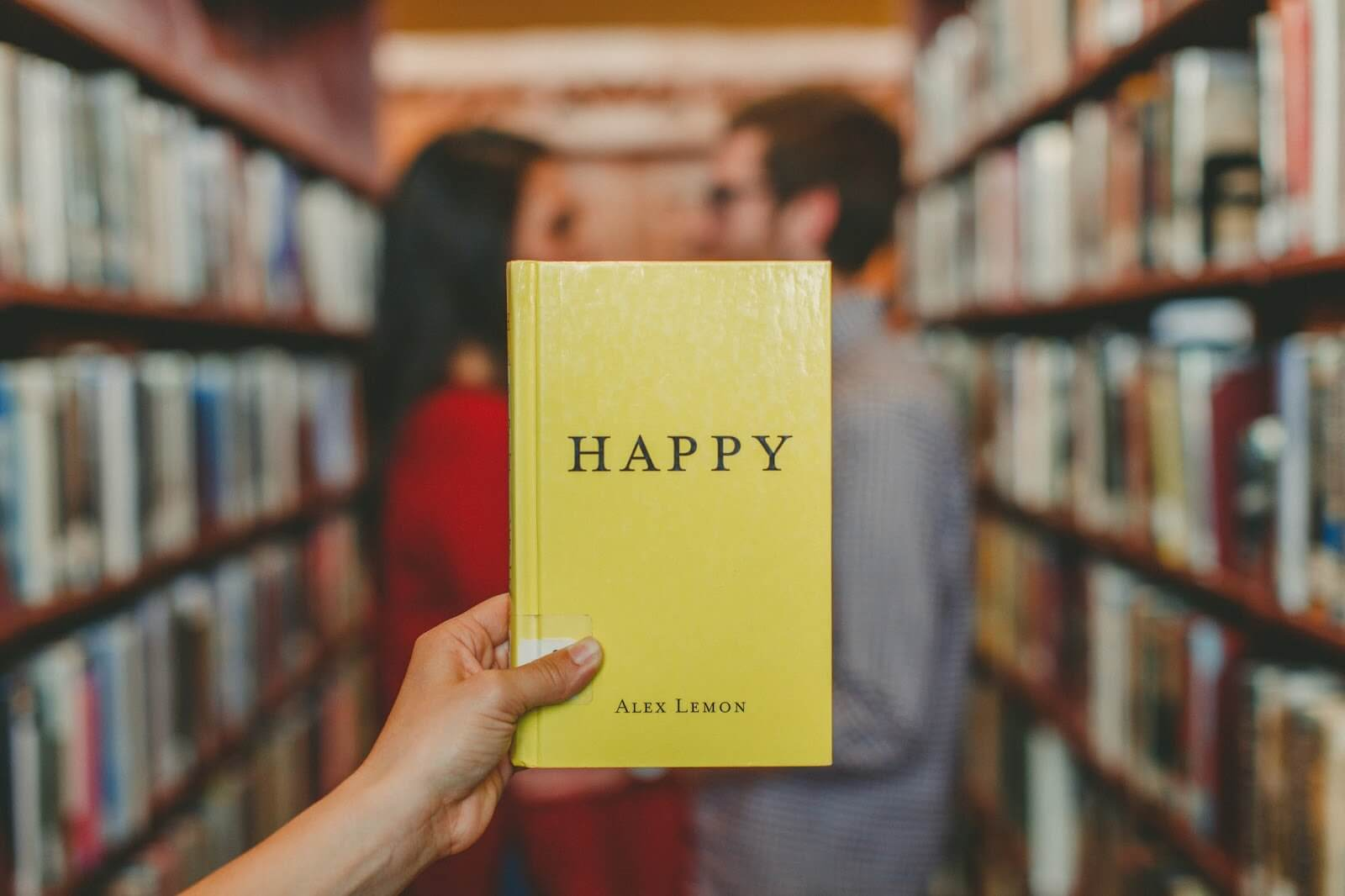relationship dilemma questions - couple in a library with someone holding up a yellow book called Happy