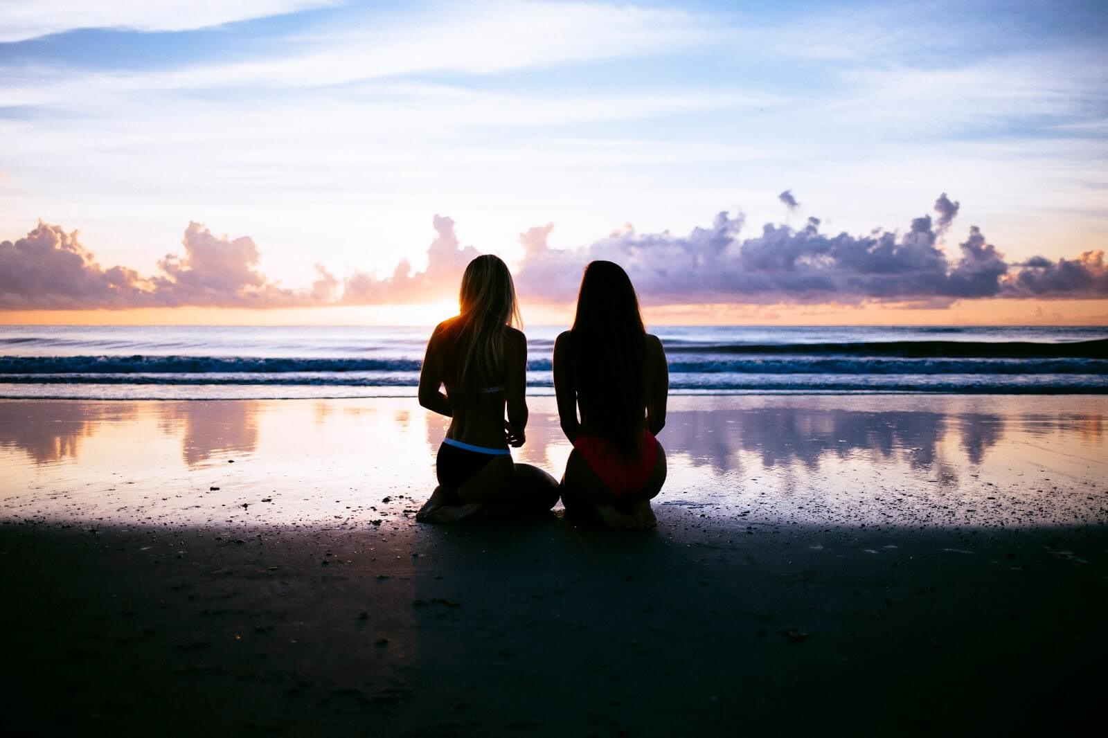What to expect in a relationship - two women sat on a beach looking at the reflection of clouds in the water