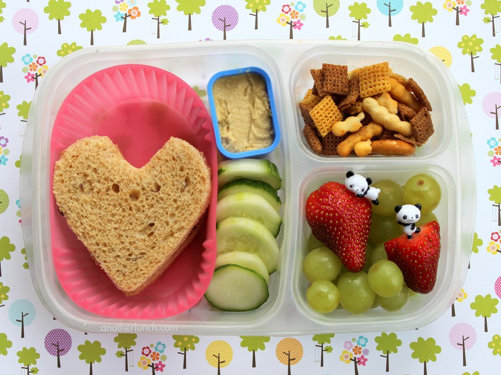 Children's lunchbox with a heart shaped sandwich, chopped veg and fruit and crackers