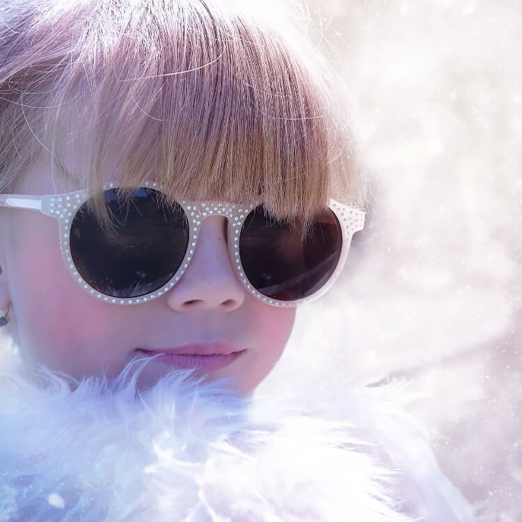 children's eyesight problems - young girl in sunglasses and a feather boa