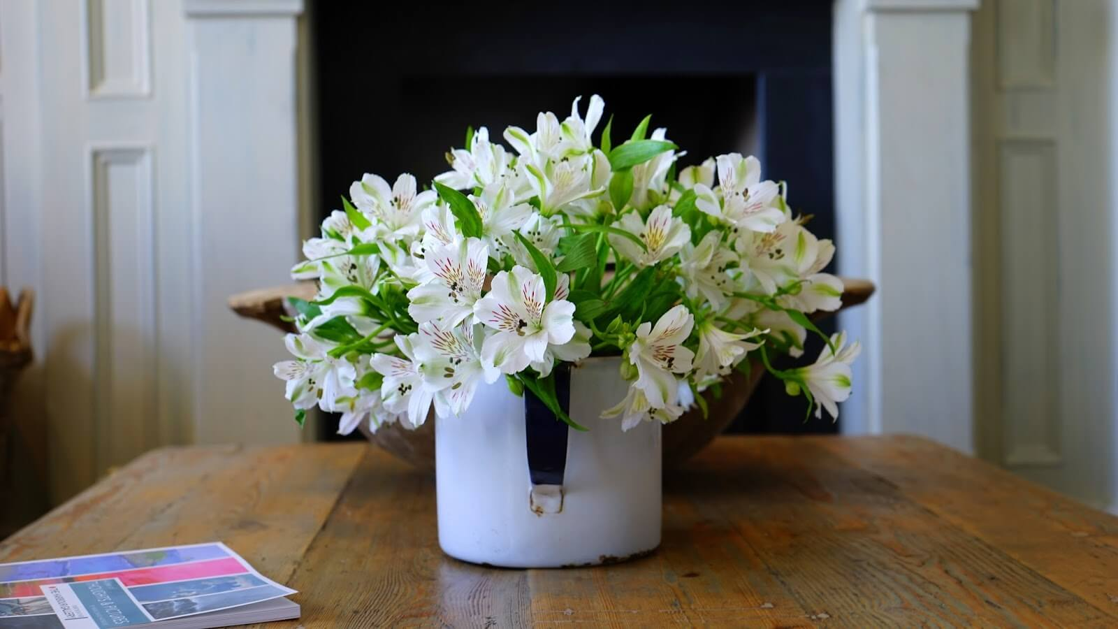 home maintenance checklist - beautiful white flowers in a vase on a wooden table