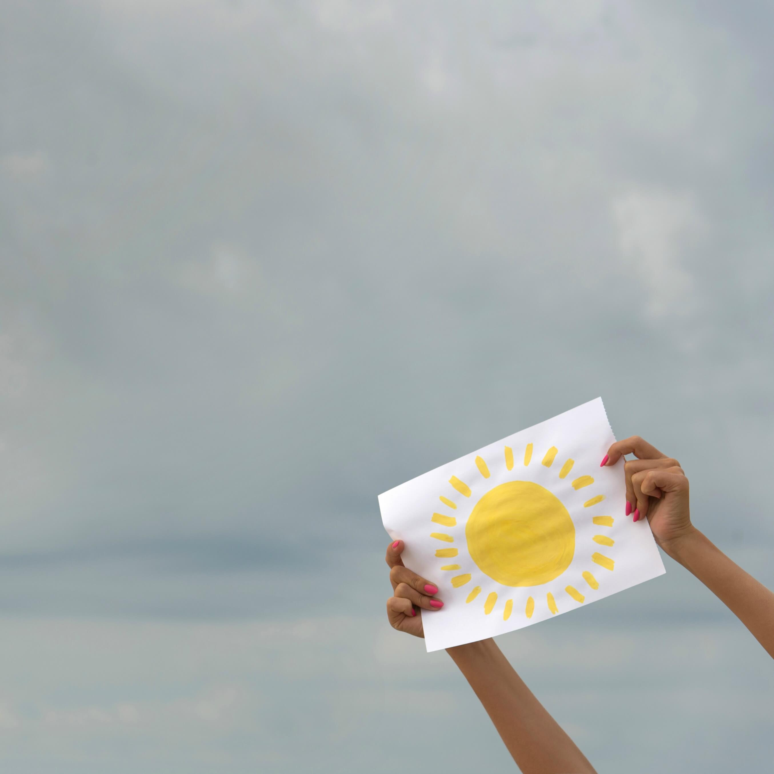 benefits of positive thinking on health - hands holding up a painted yellow sun against a grey sky