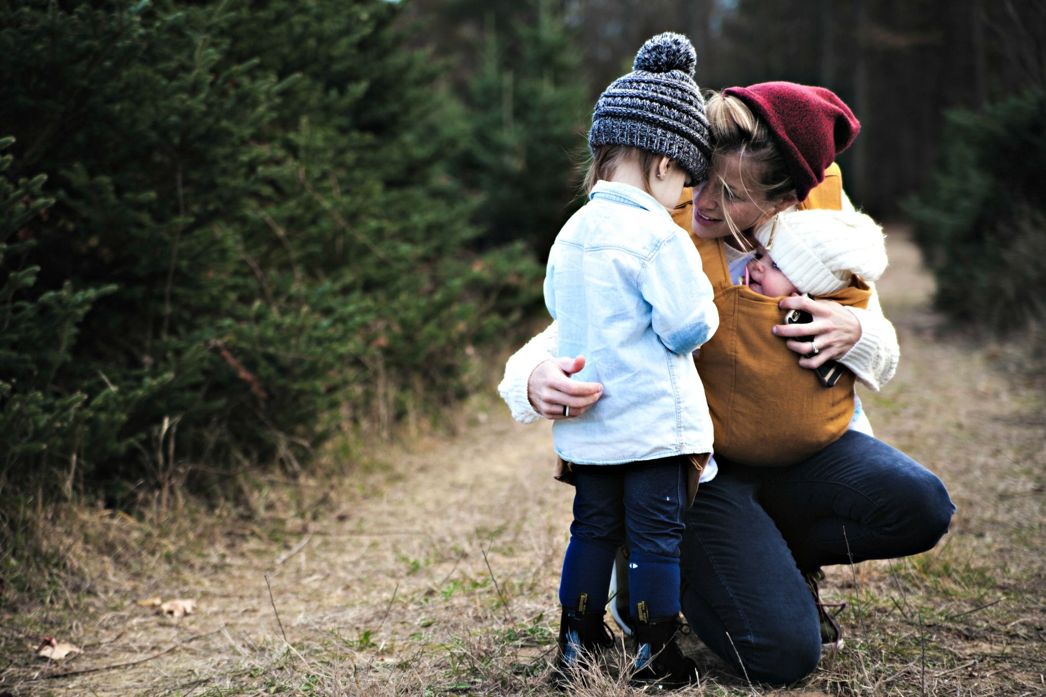 mum outdoors cuddling her two children - how to be a calmer parent