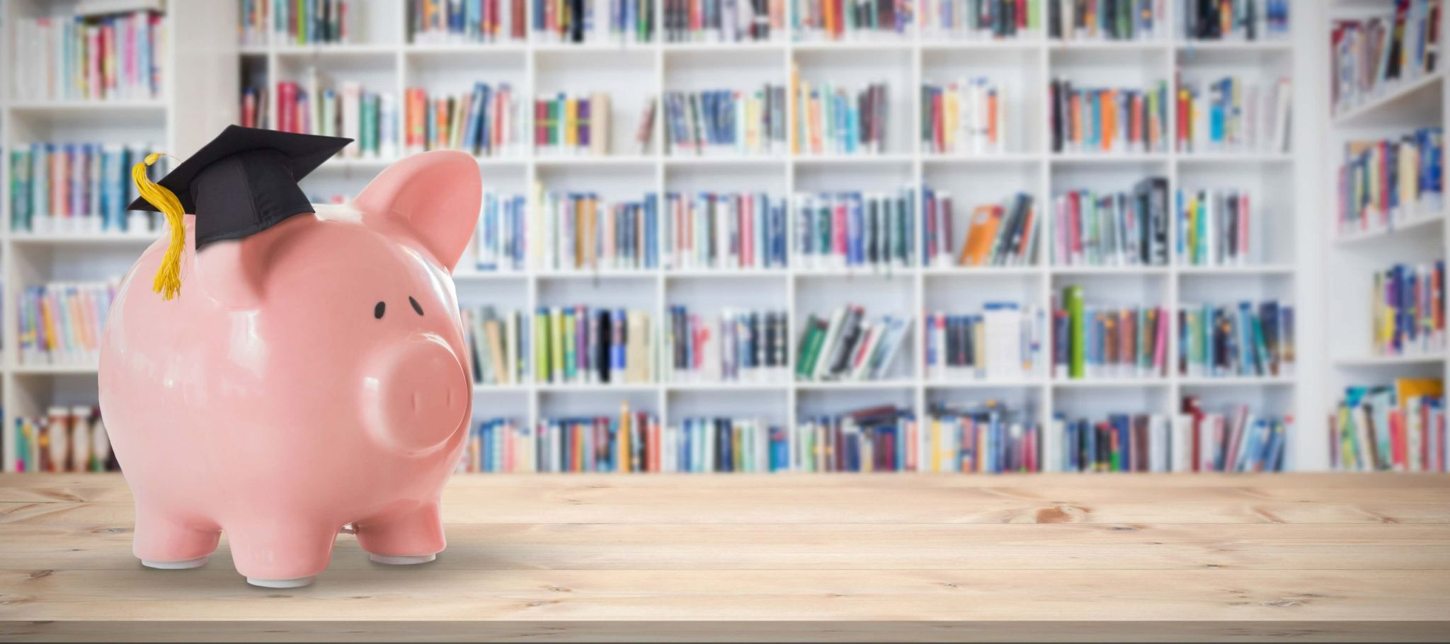 fun money lessons - a piggy bank wearing a graduation hat in a library