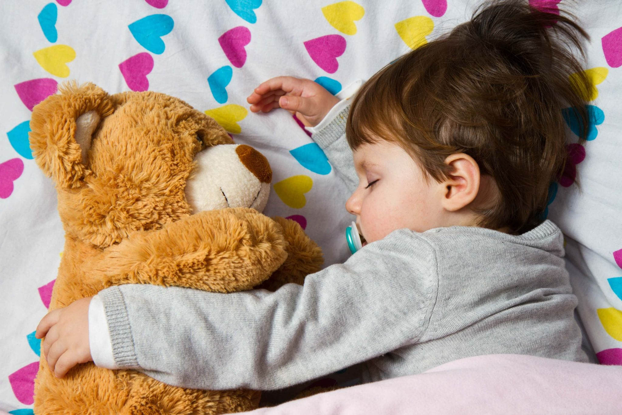 help children sleep in the heat - little boy asleep cuddling a teddy bear