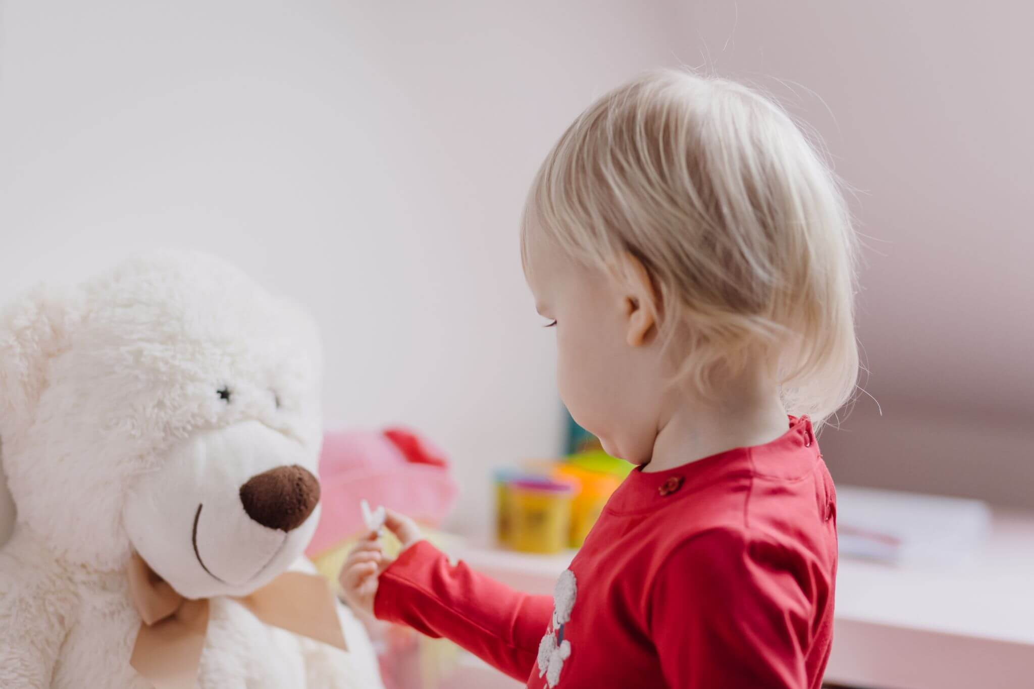 get your home ready for autumn - little girl playing with a teddy