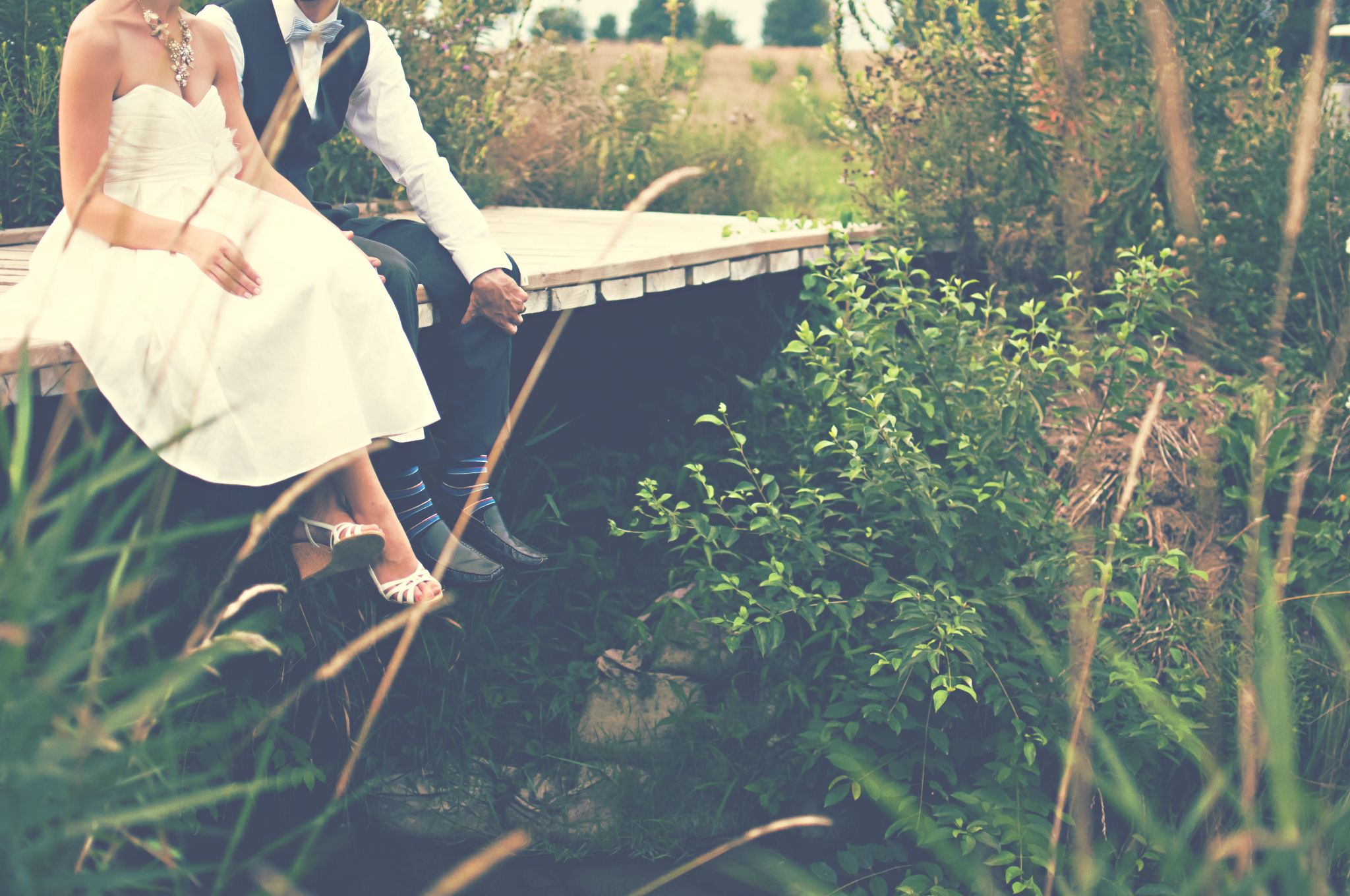 bride and groom holding hands sat on a wooden bridge, rekindle your romance tips, motherdistracted.co.uk
