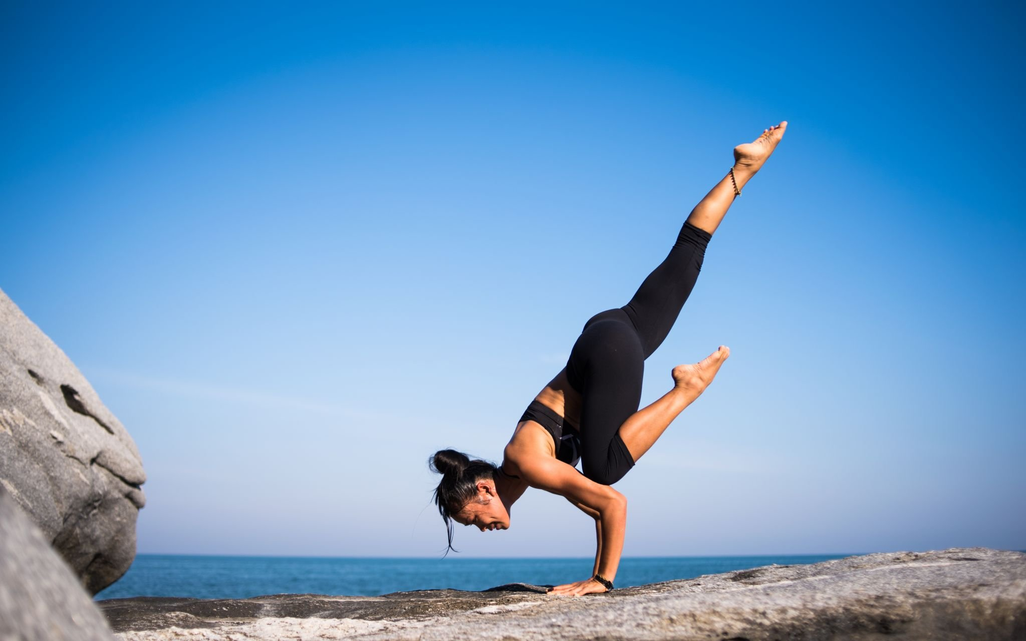 woman doing yoga pose on a clifftop