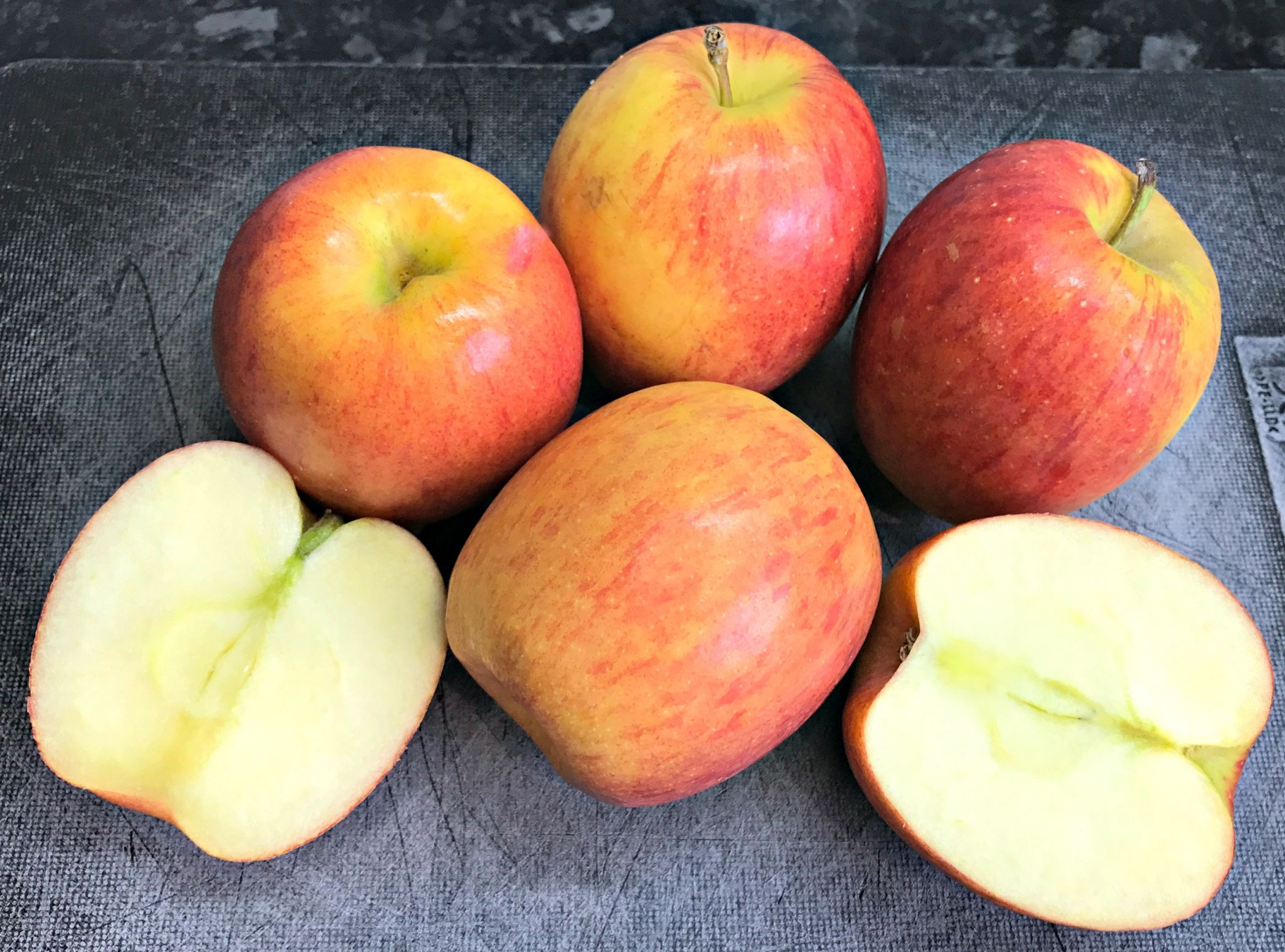 Jazz Apples on a black chopping board