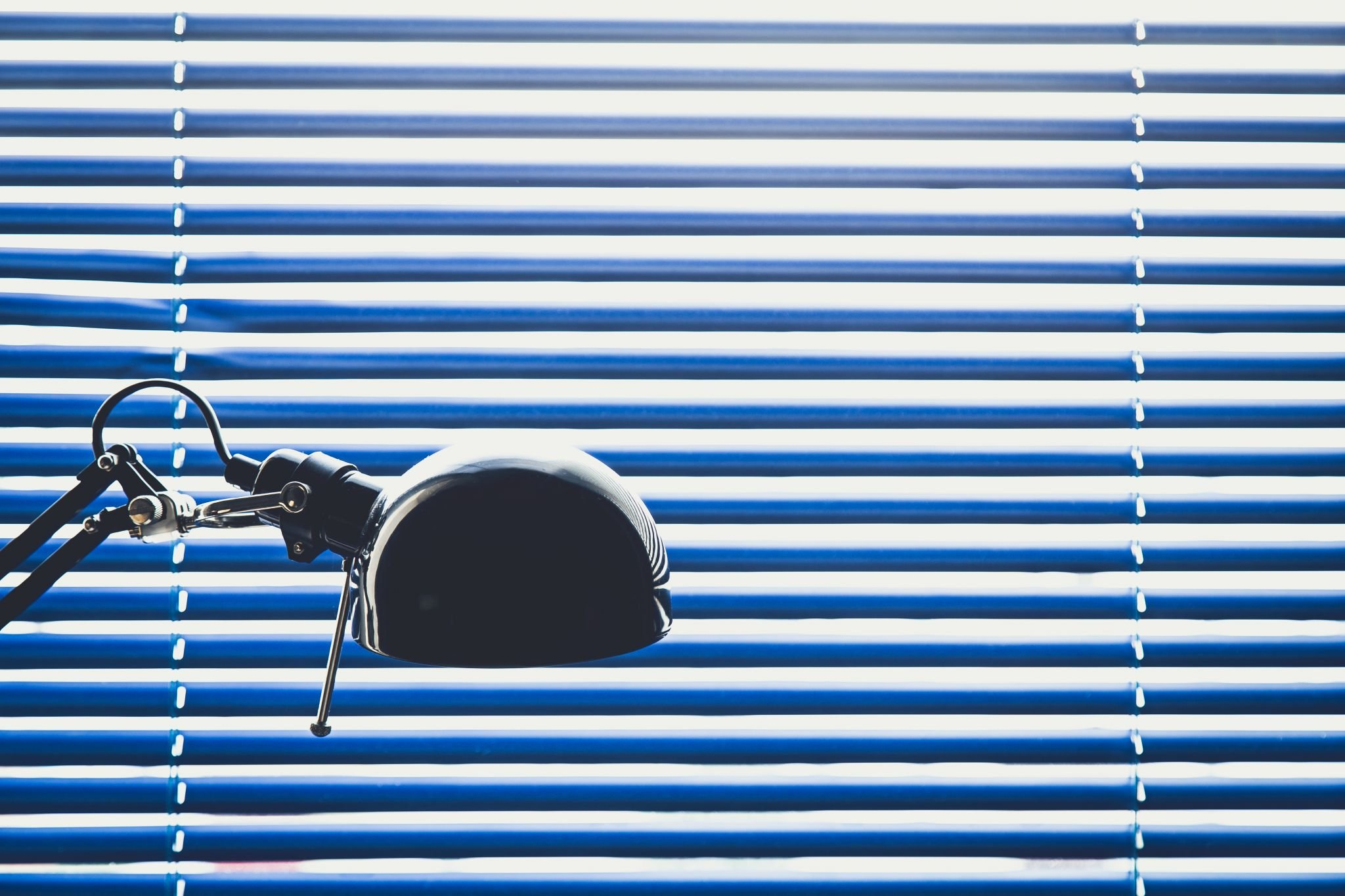 Desk light infront of blue venetian blind
