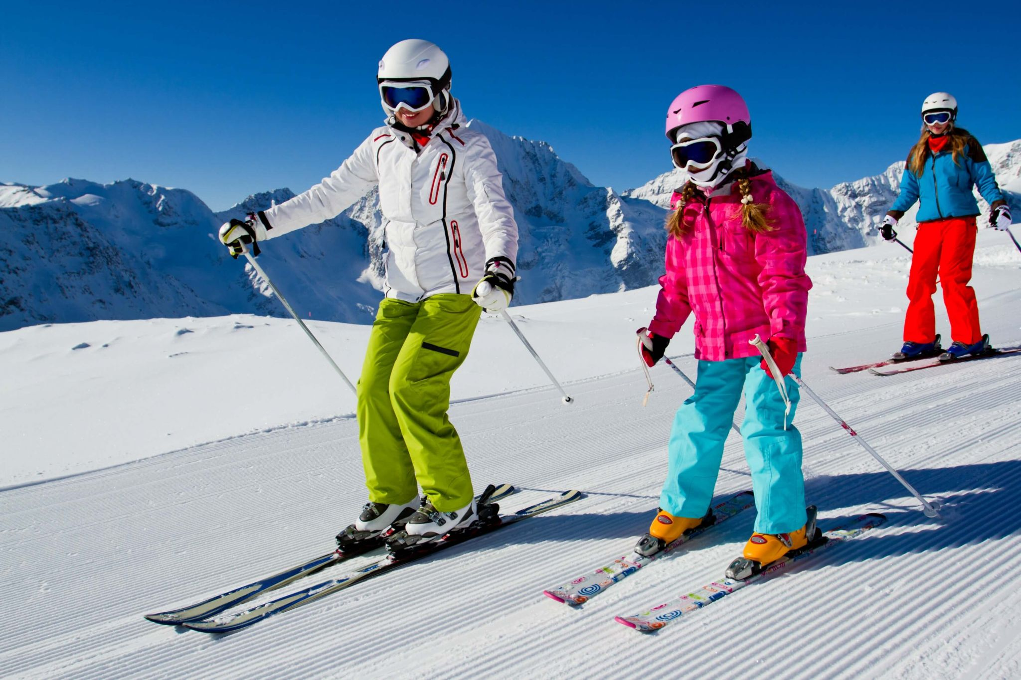 ski holiday with kids - family skiing on the piste