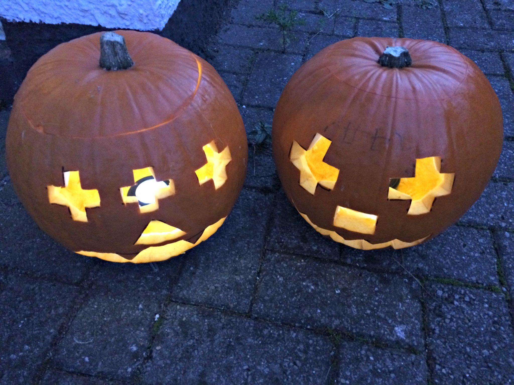 2 carved and lit Halloween pumpkins