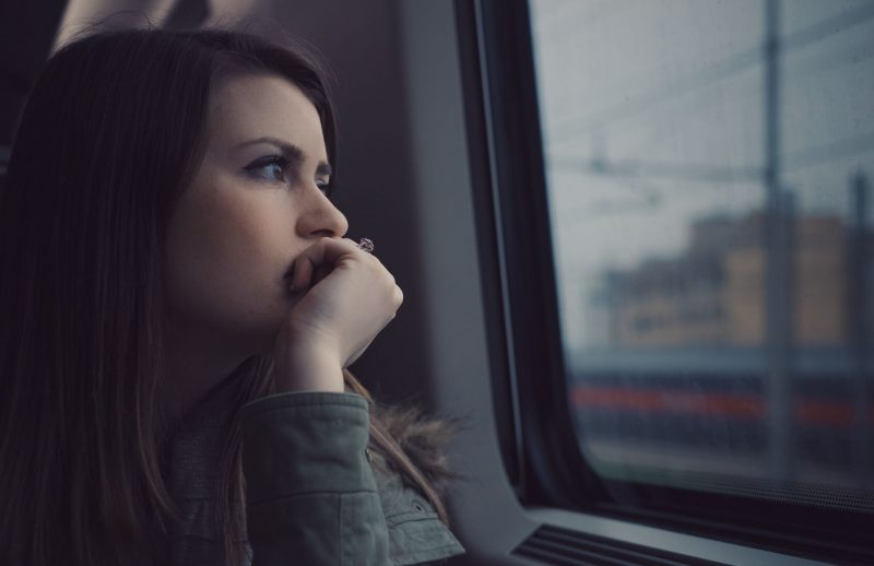 Woman with her chin on her hand looking pensive