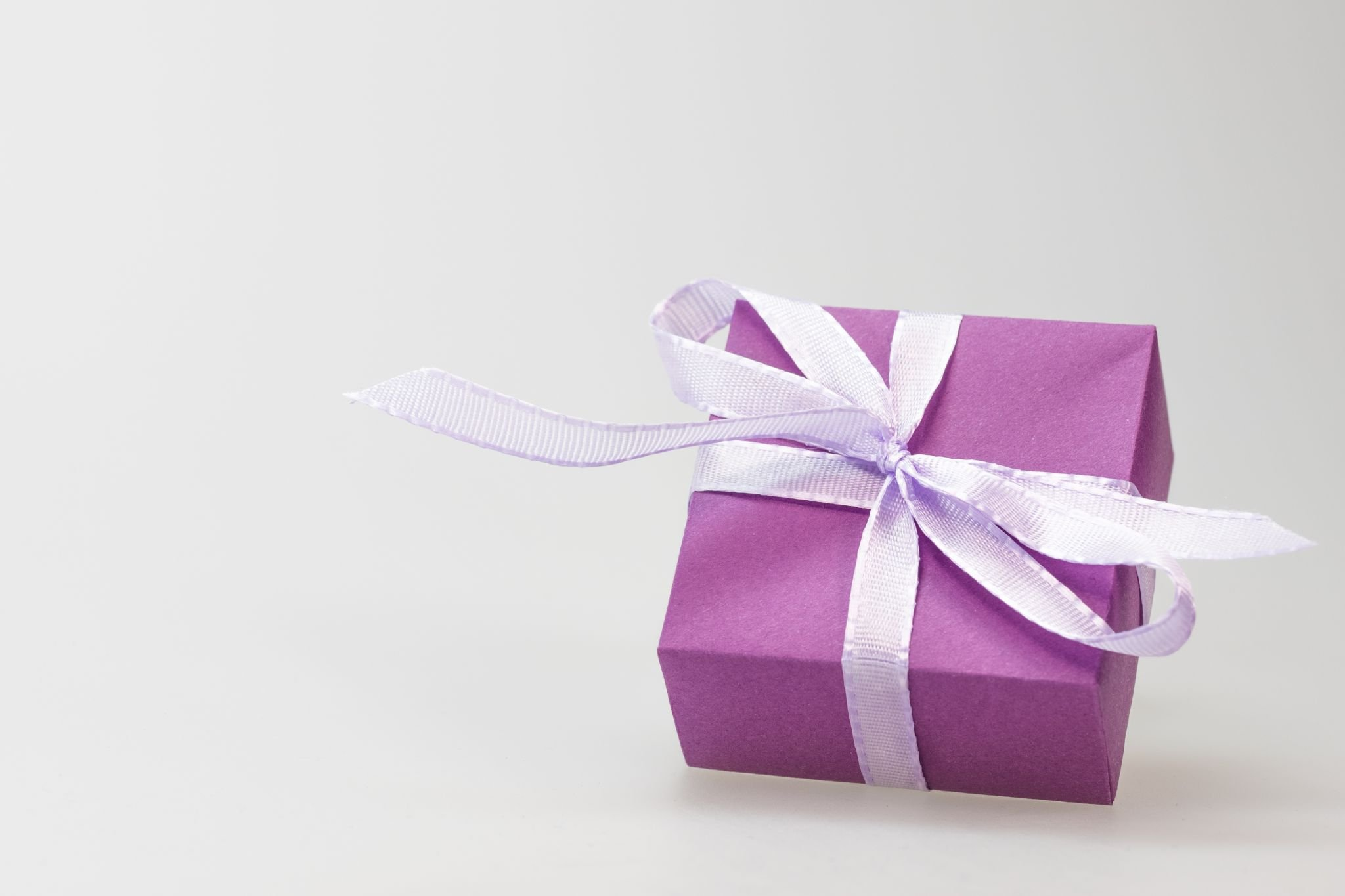 Small purple gift box with white ribbon