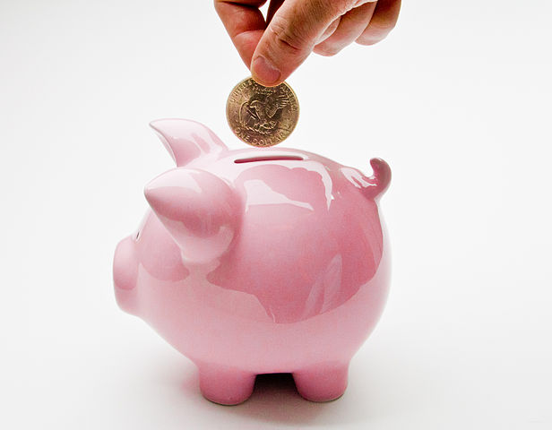 Hand placing a coin into a pink piggybank