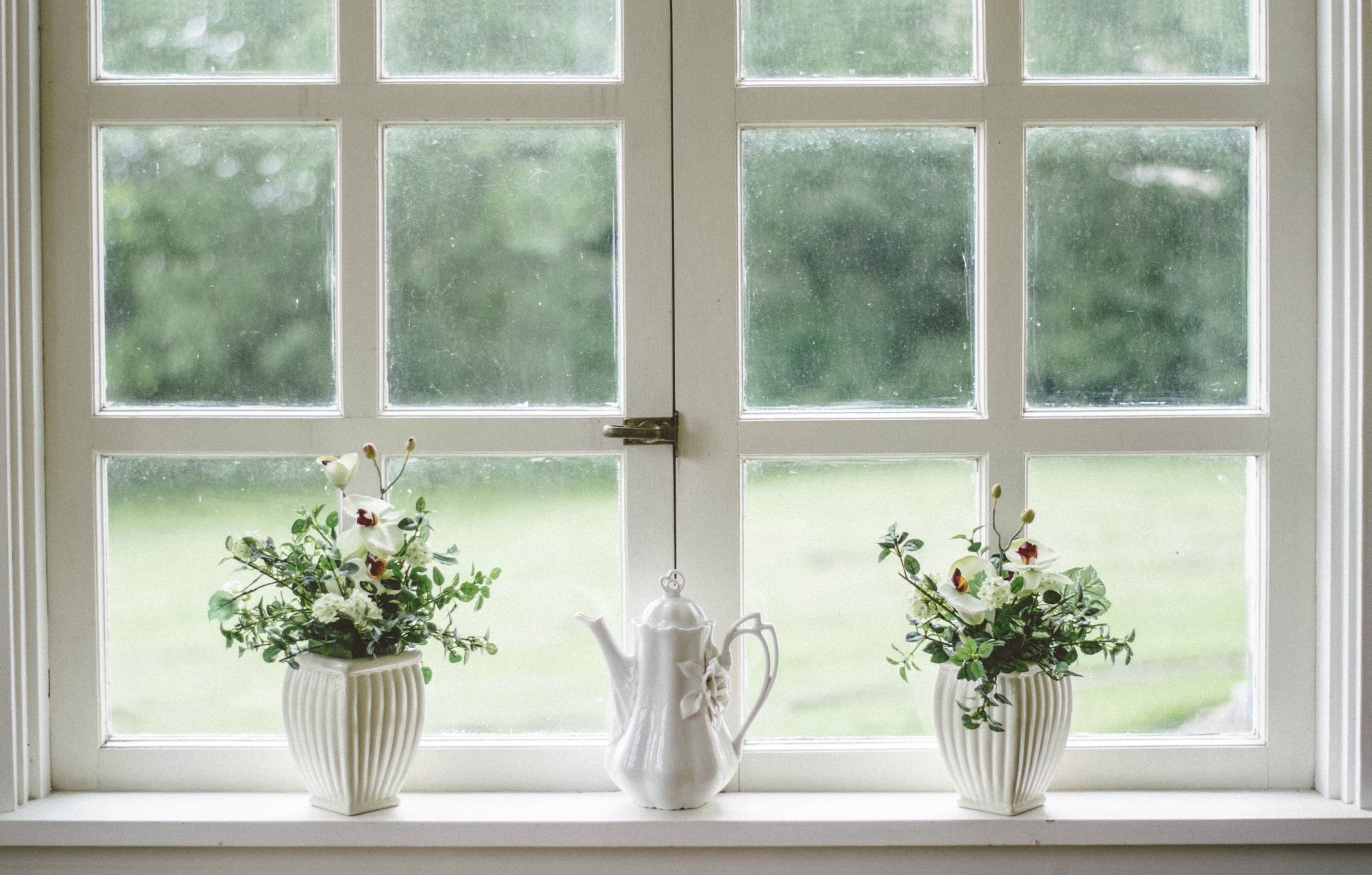 Go for big relaxation with a good declutter - three potted plants on a window sill in white pots