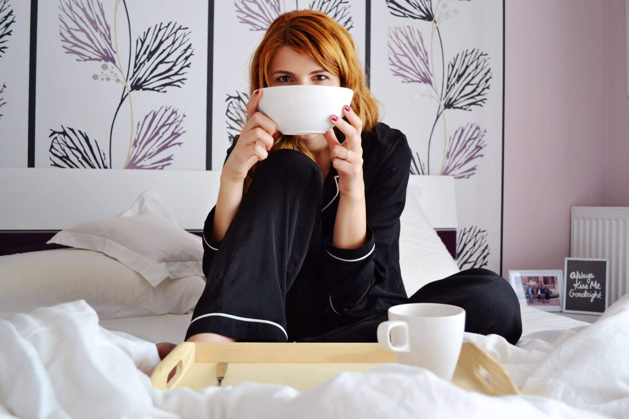 size of a super king size bed - woman drinking coffee sitting on a bed in her pyjamas