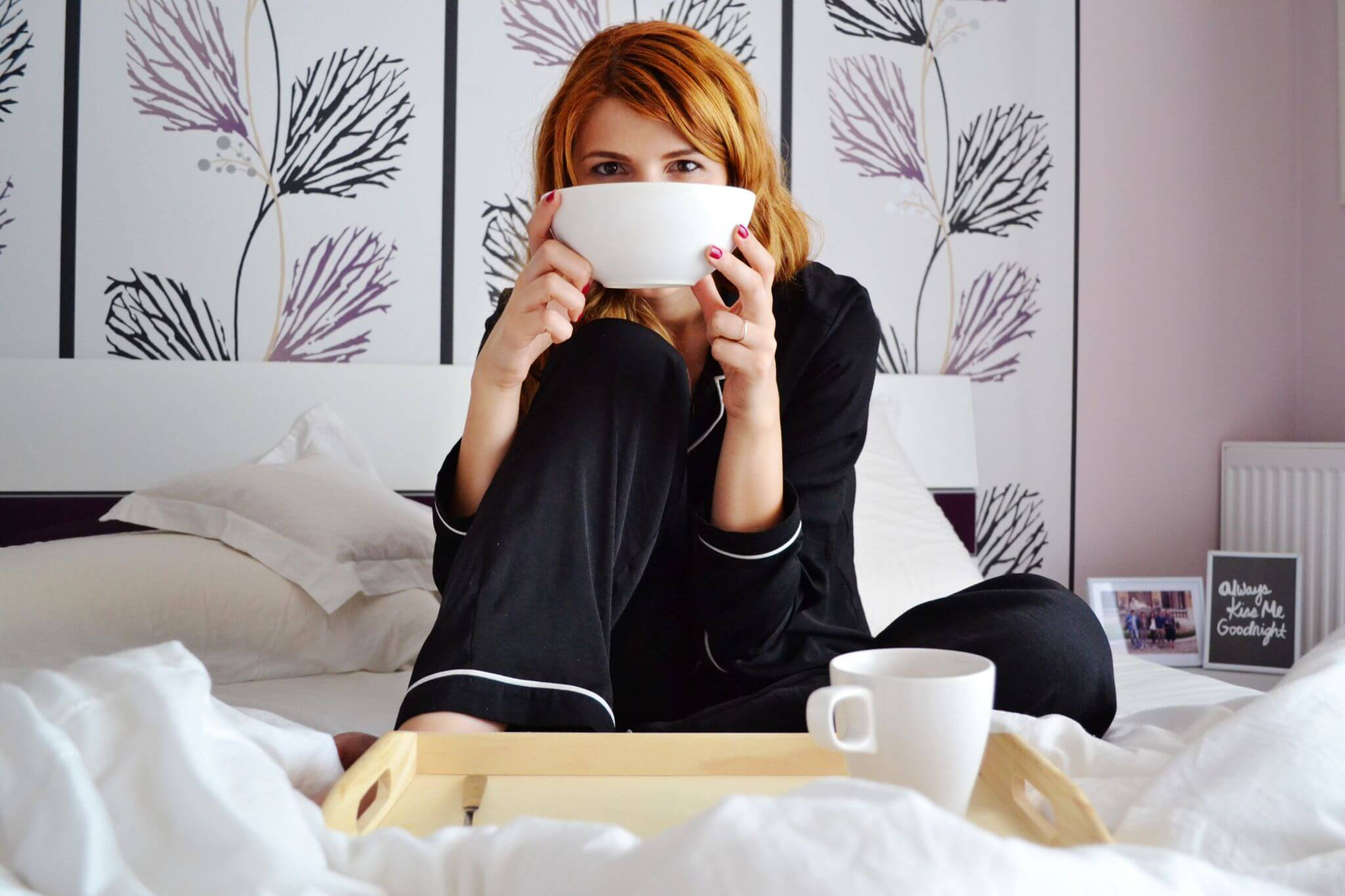 sleep better with a bigger bed - woman on big white bed wearing black pajamas and drinking coffee from a big white cup