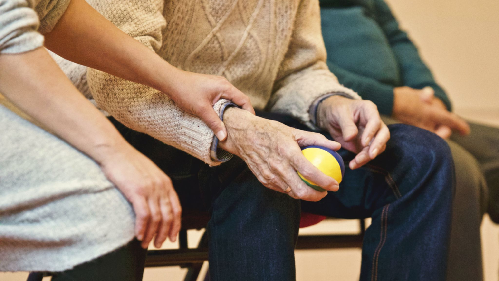 Early signs of dementia - old man holding a ball. Lady next to him comforting him.