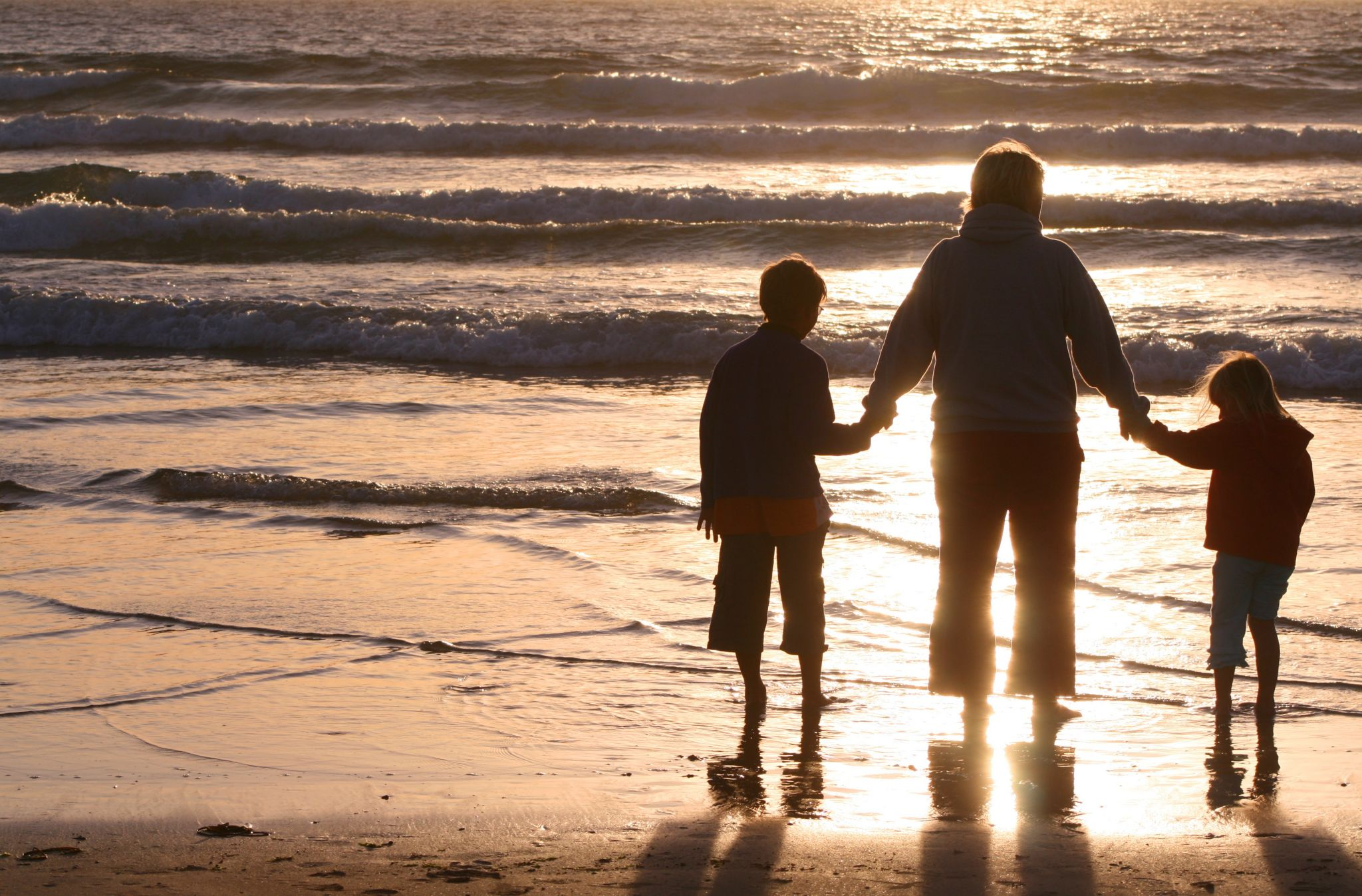 winter family travel health tips - man on beach with 2 children