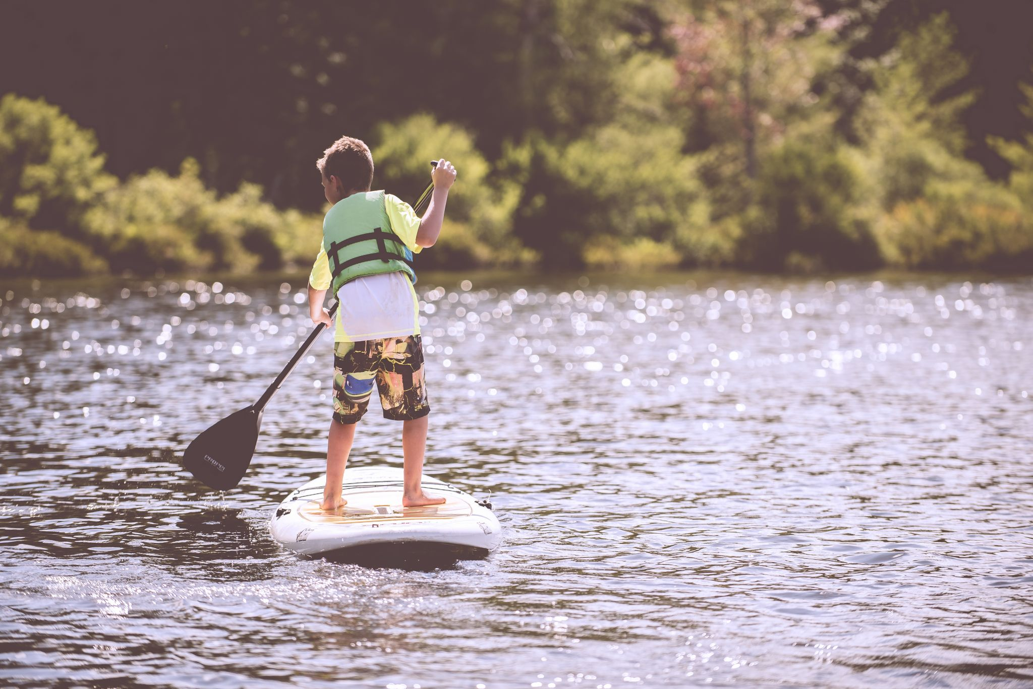 Young boy on a paddle board in a river - getting your kids to join a kids' club could make their holiday