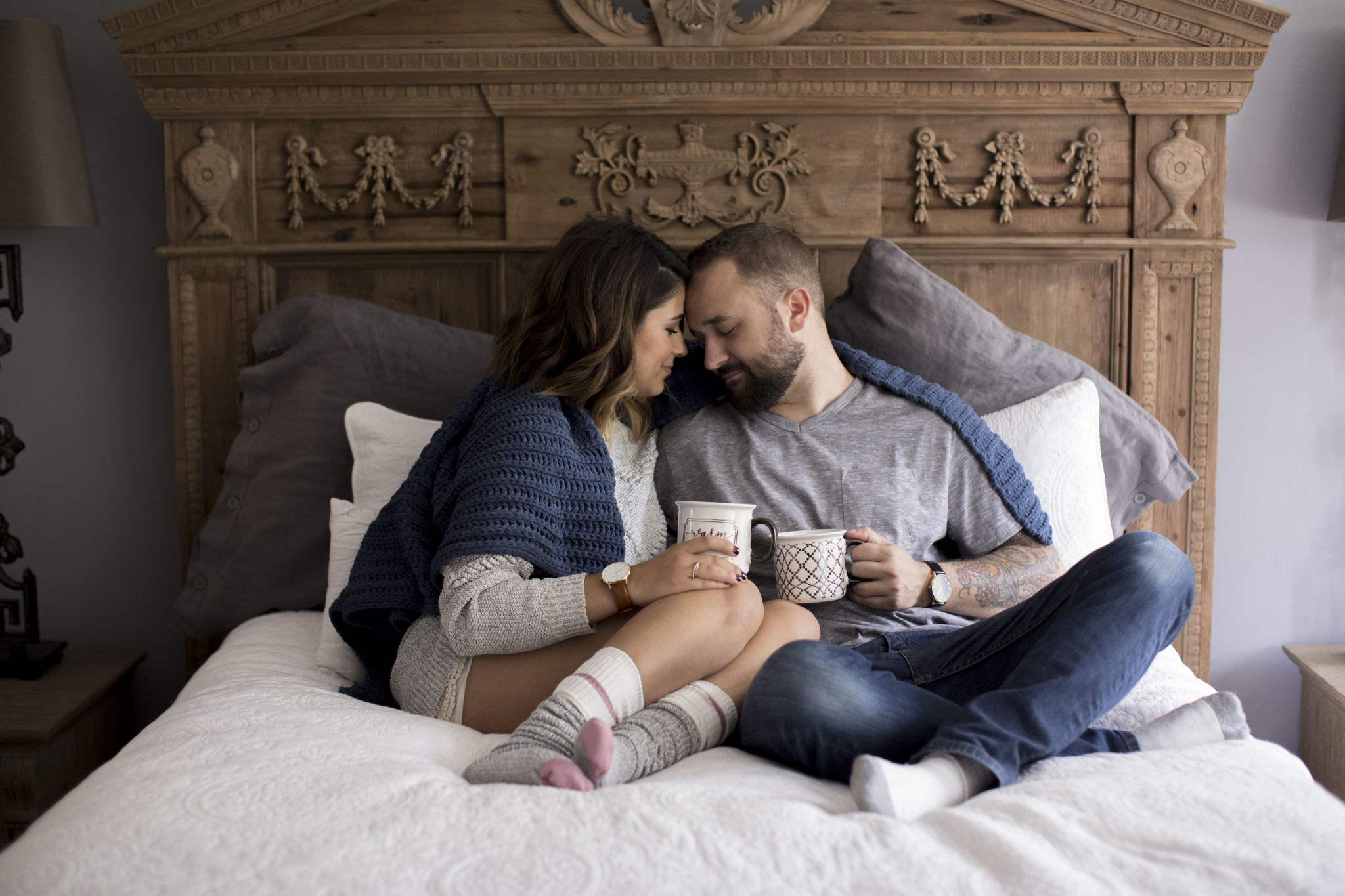 Couple snuggled up on bed drinking coffee and wearing Charles Conrad watches