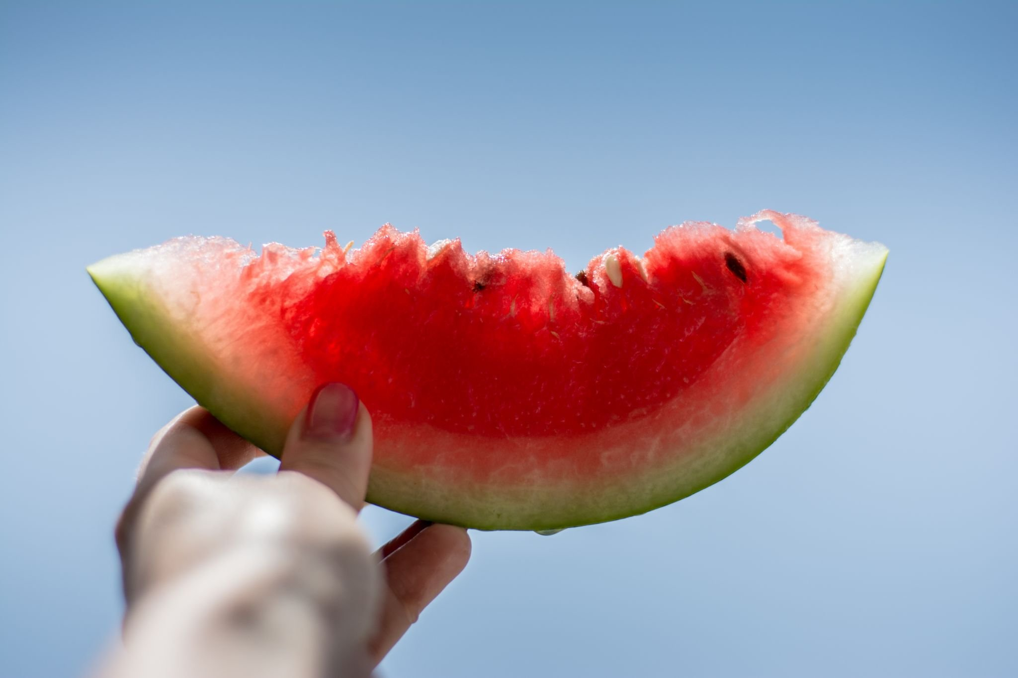 Slice of watermelon being held up by a woman's hand - The 4 Pillar Plan