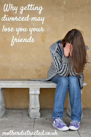 losing friends after divorce - woman on a stone bench with her head in her hands