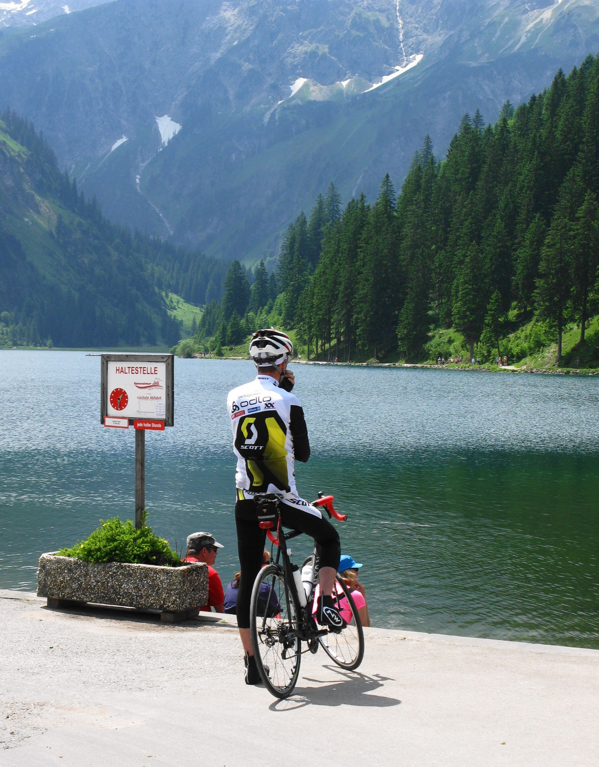 mountain biker resting looking at a lake - reasons to visit the alps