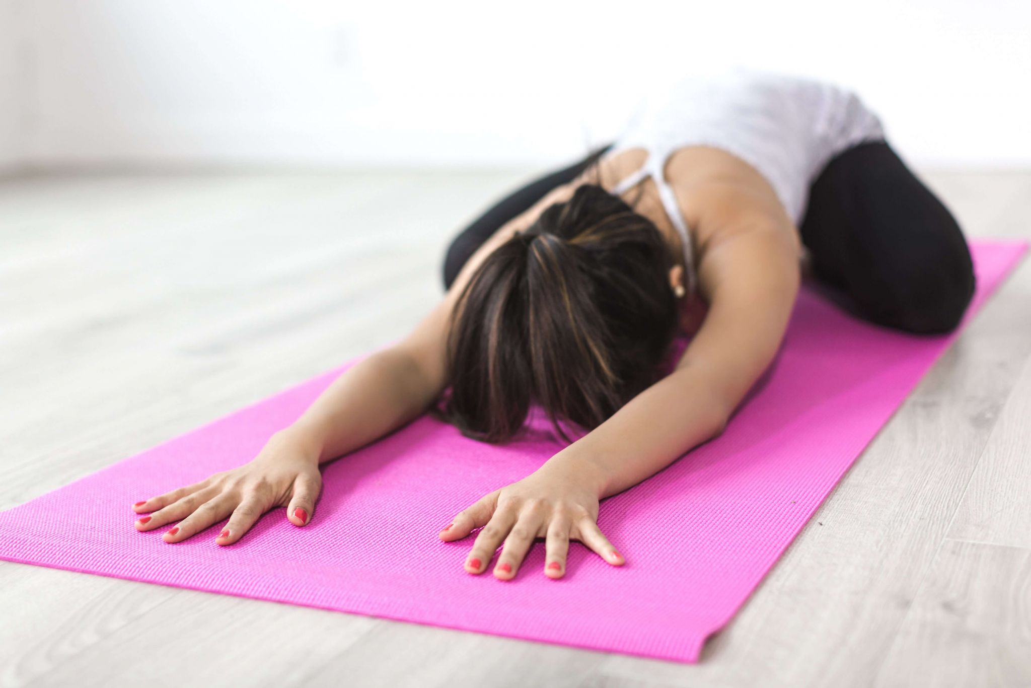 fitness is an activity that can be squeezed into a busy day - woman stretching on a mat