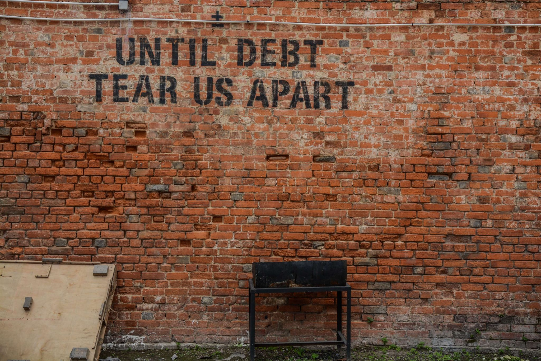 "money affects relationships - graffiti on an old stone wall saying ""until debt tear us apart"""