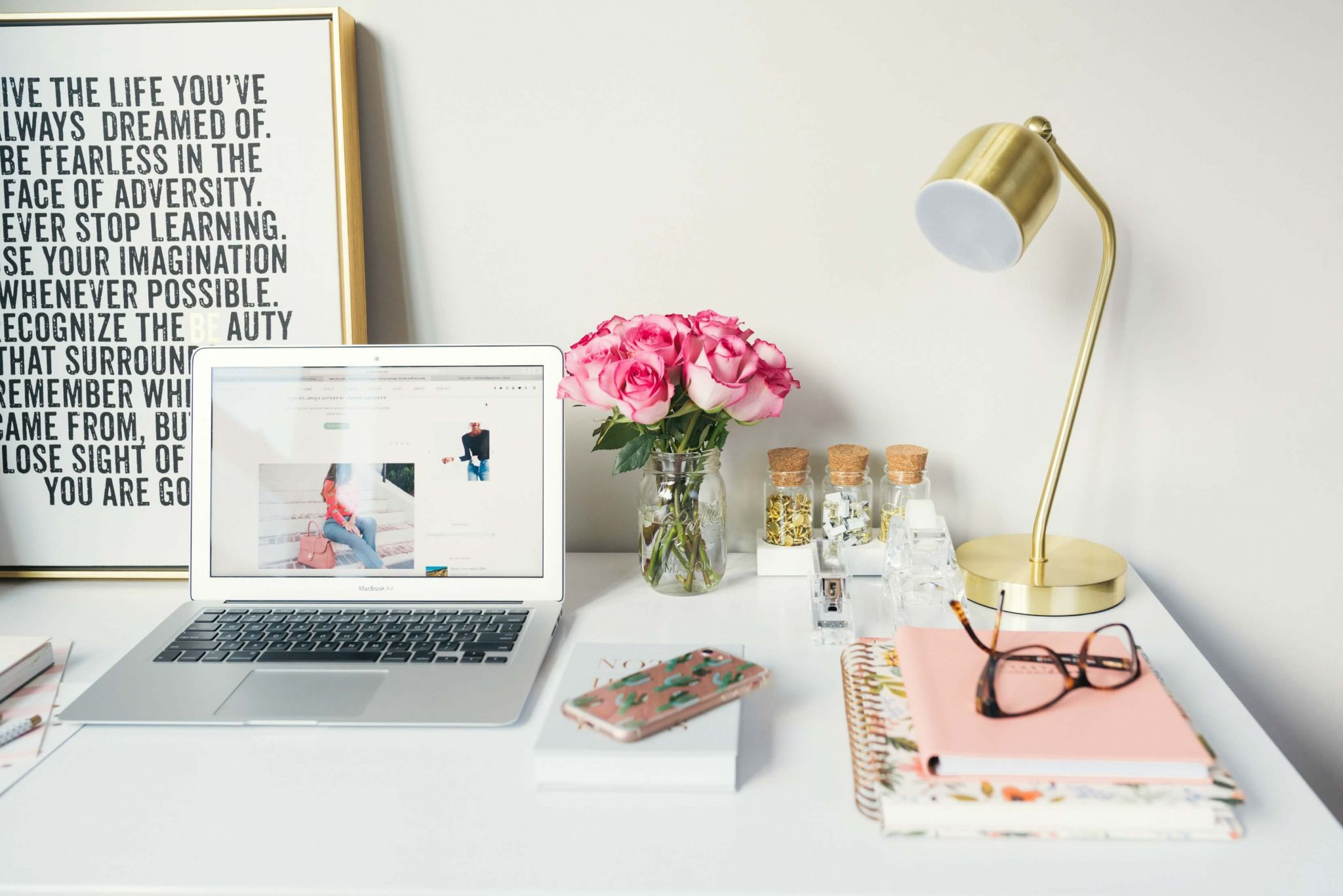Turning your blog into a business - blogger's desk with laptop, motivational print, glasses, pink notepad and flowers