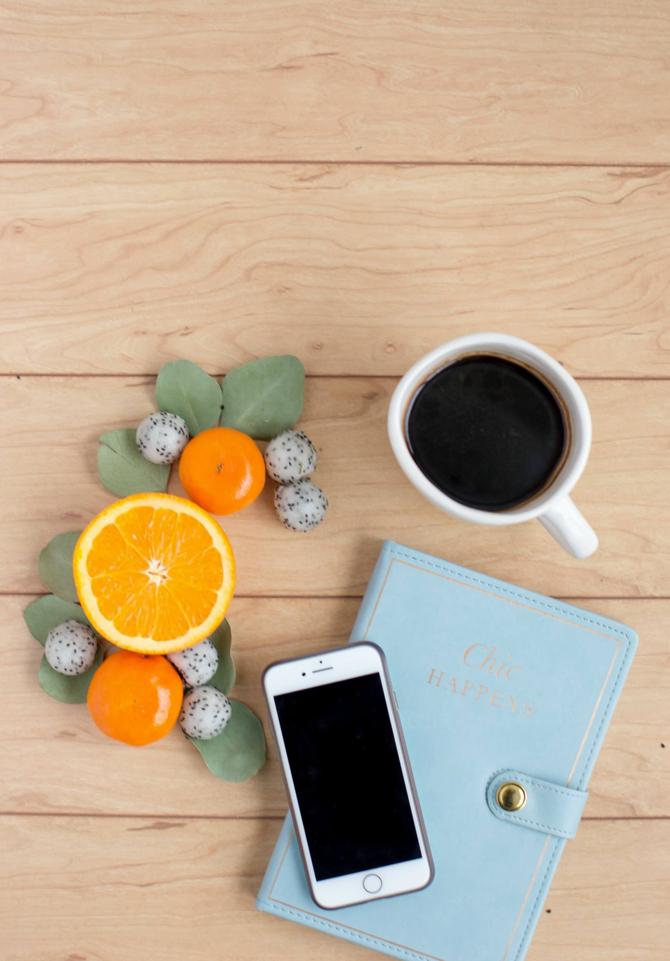 lifestyle mobile apps - coffee, planner and fruit on a wooden background