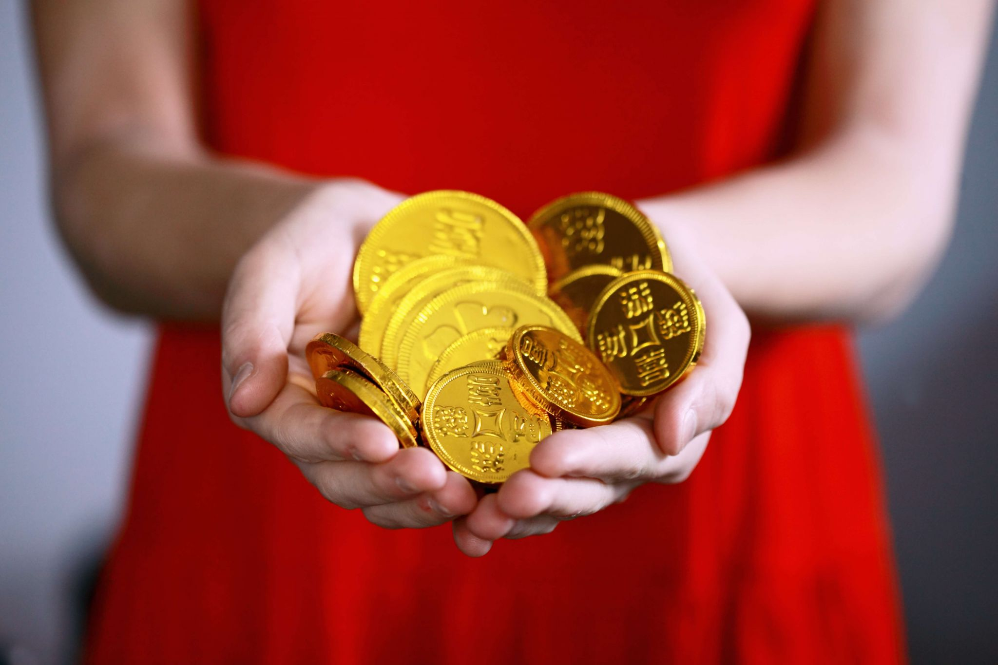 How to store collectibles - woman in red dress with her hands full of gold coins