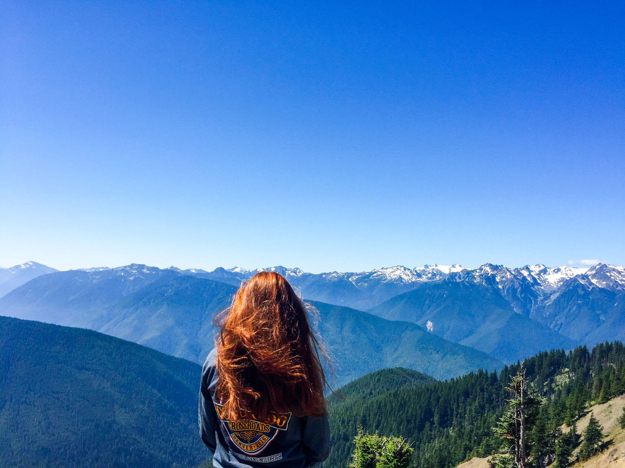 problem page edition 17 - woman with long red hair staring out at the mountains under a bright blue sky