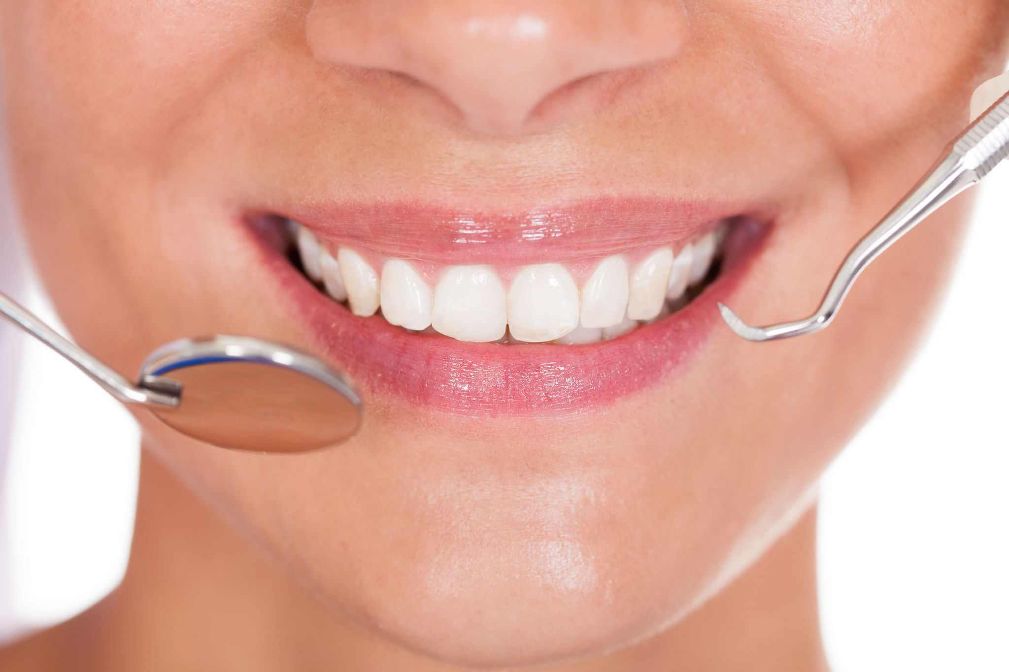 keep your gums healthy - woman's smiling mouth with white teeth and dental implements