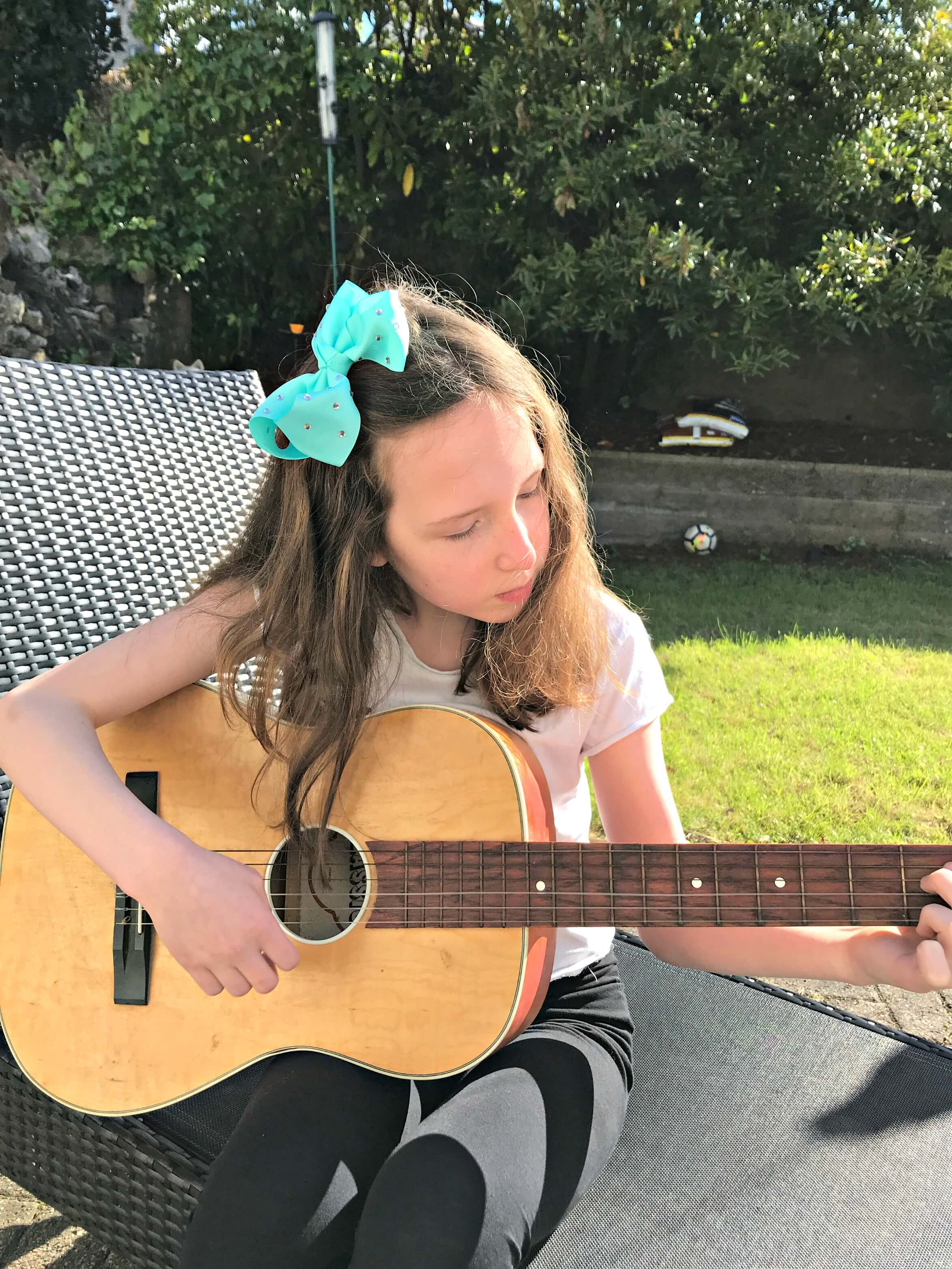 learn to play the guitar - Caitlin playing guitar in the garden at home