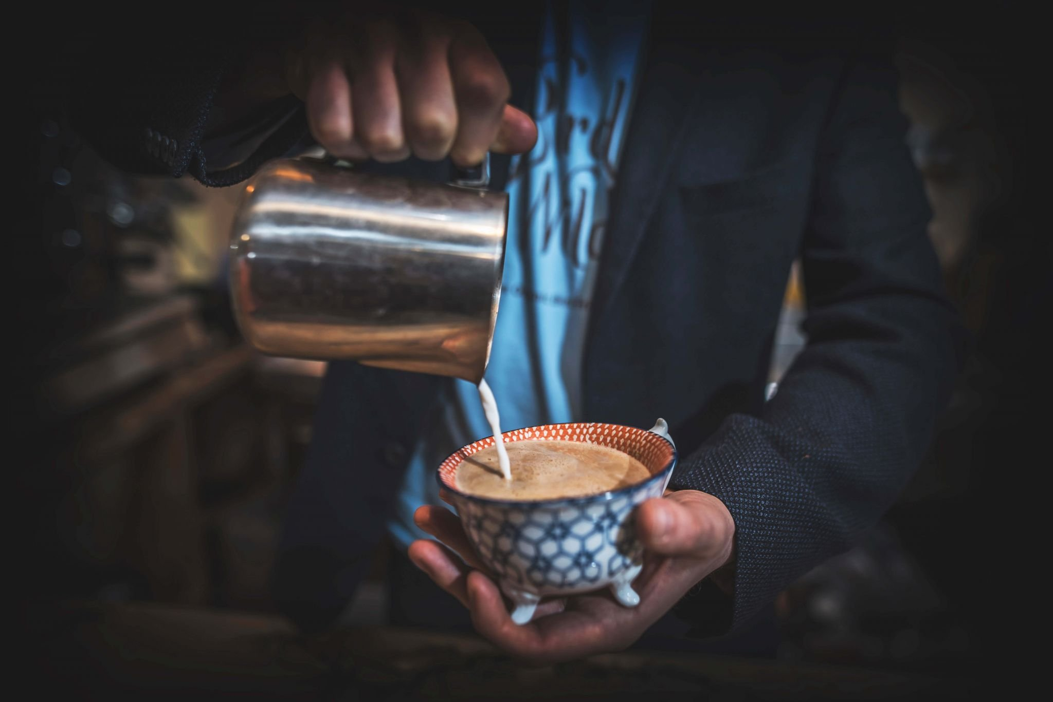 speciality coffees - milk being poured into a coffee