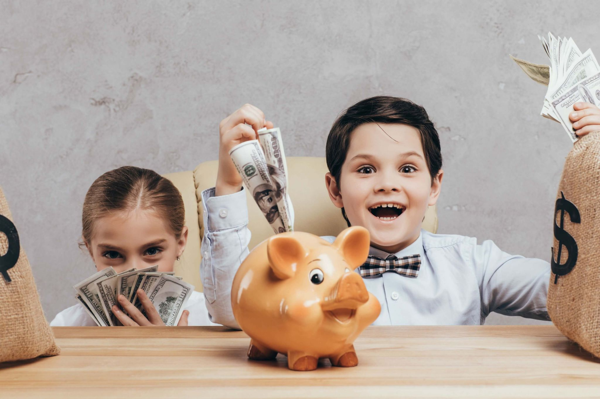 teaching financial literacy to kids - little girl and boy playing with wads of dollars and a piggy bank