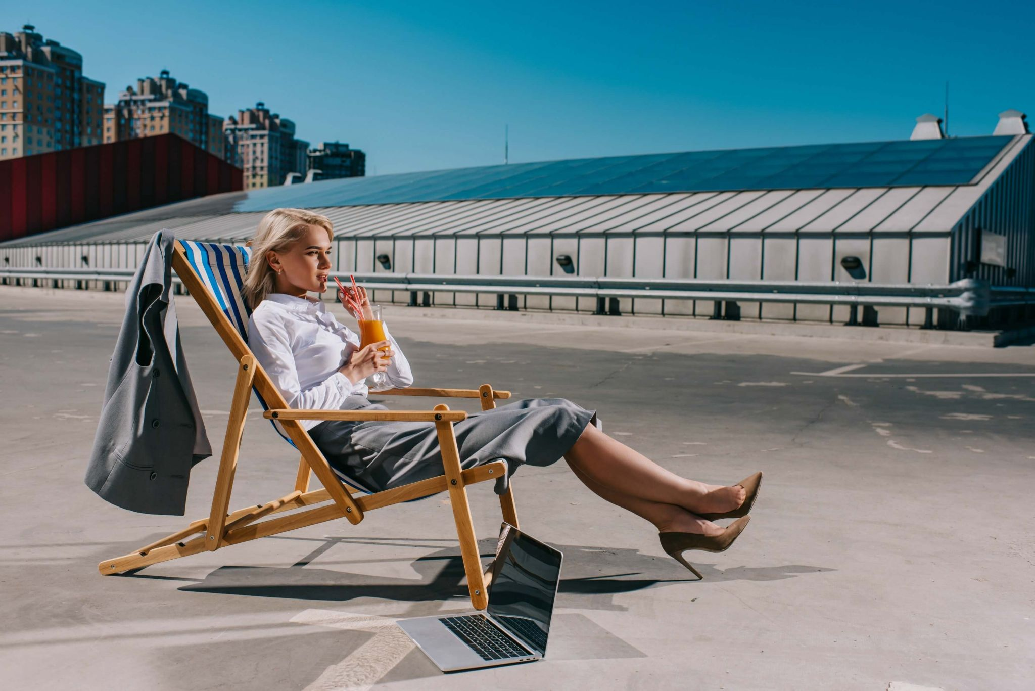 tips to stay cool in the heat - woman on top of an office block in a deckchair
