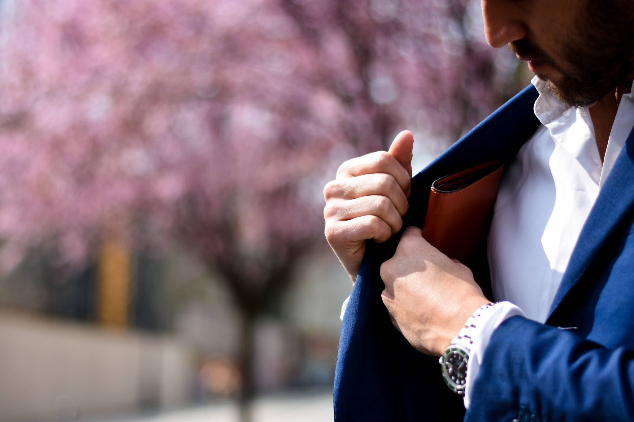 Debt management plan - man in a blue suit putting his wallet away