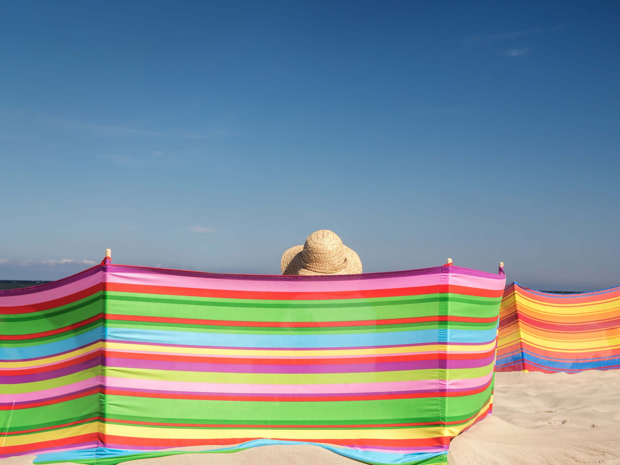 what to take to the beach - woman in a straw sunhat sat behind a multicoloured windbreak on a beach