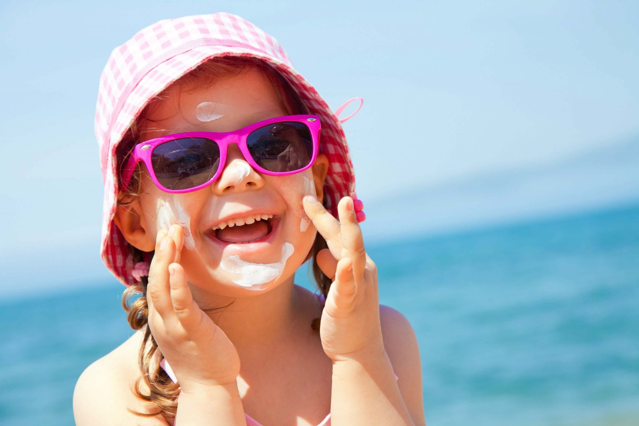 stay safe in the sun - little girl applying suncream to her face on a beach