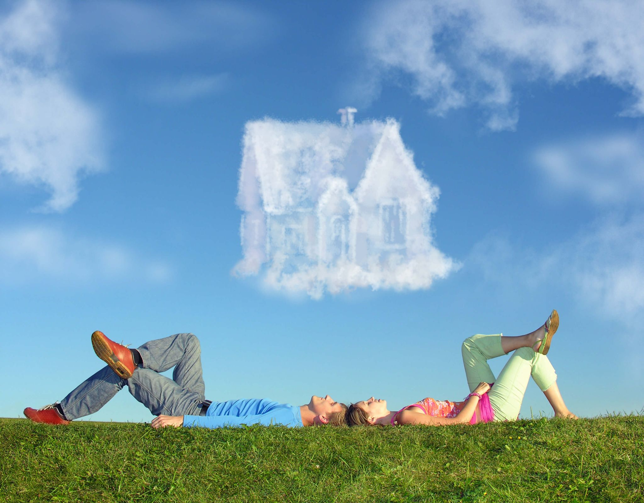 help to buy - couple lying on the grass looking at the image of a house in the clouds